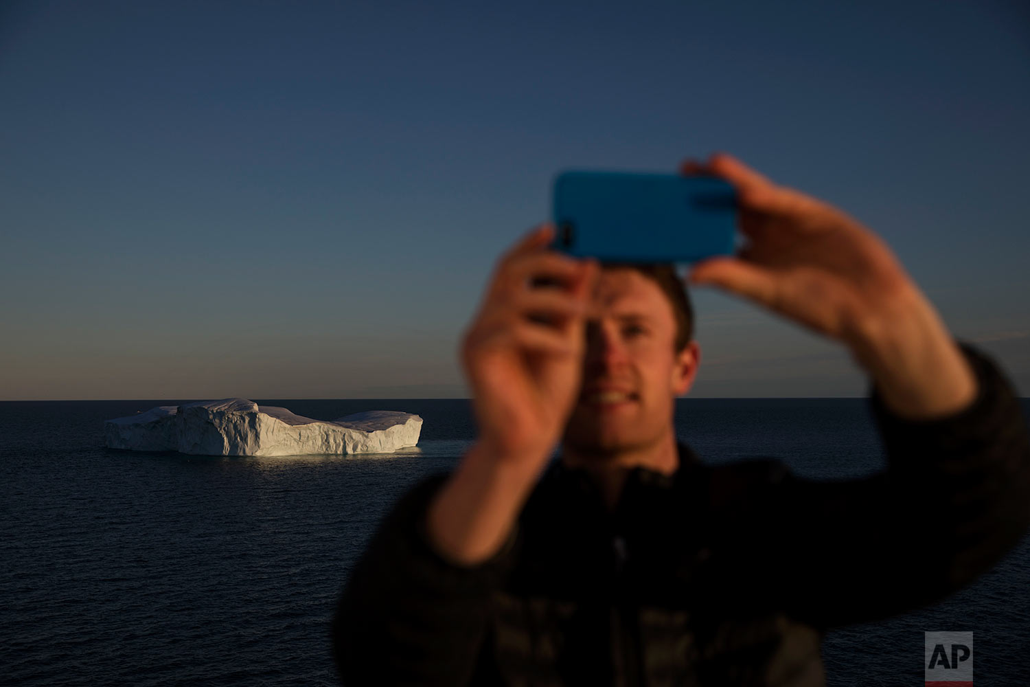 Researcher Scott Joblin takes a selfie while passing an iceberg floating in Baffin Bay in the Canadian Arctic Archipelago while aboard the Finnish icebreaker MSV Nordica, Tuesday, July 25, 2017.(AP Photo/David Goldman)