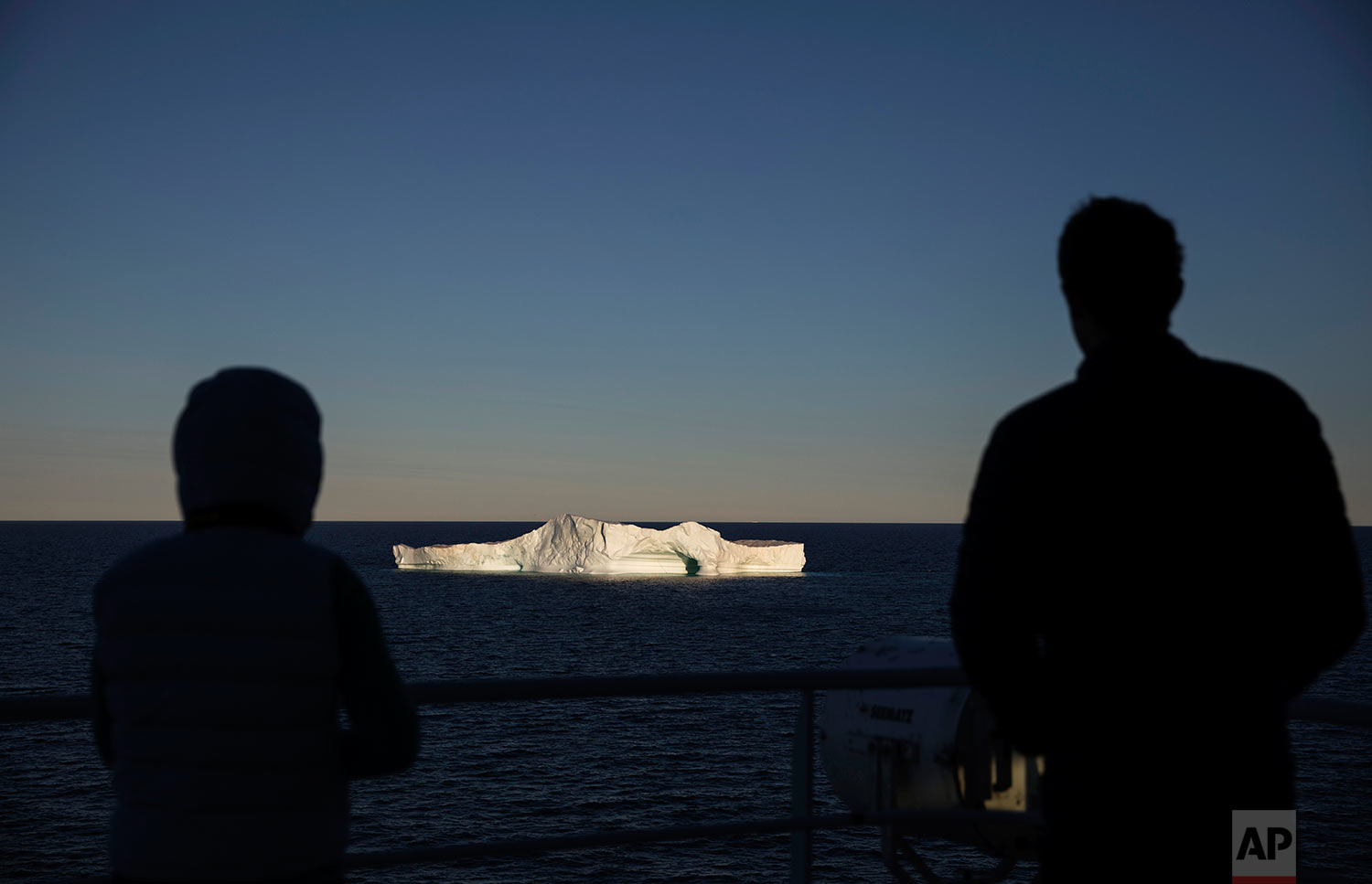Researchers aboard the Finnish icebreaker MSV Nordica watch while approaching an iceberg floating in Baffin Bay in the Canadian Arctic Archipelago, Tuesday, July 25, 2017.  (AP Photo/David Goldman)