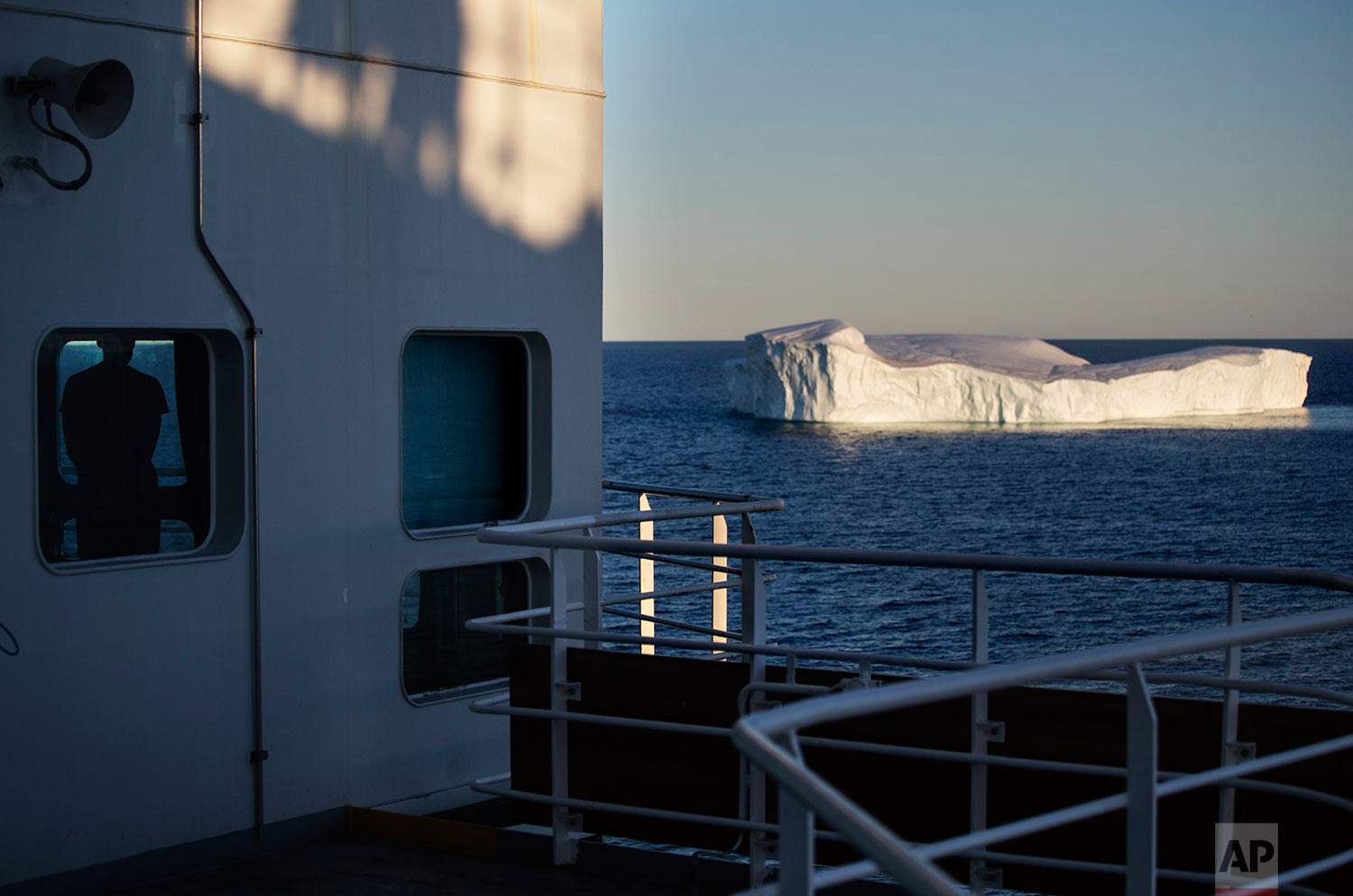 Trainee David Kullualik, left, looks out a window of the Finnish icebreaker MSV Nordica at an iceberg floating in Baffin Bay in the Canadian Arctic Archipelago, Tuesday, July 25, 2017. (AP Photo/David Goldman)