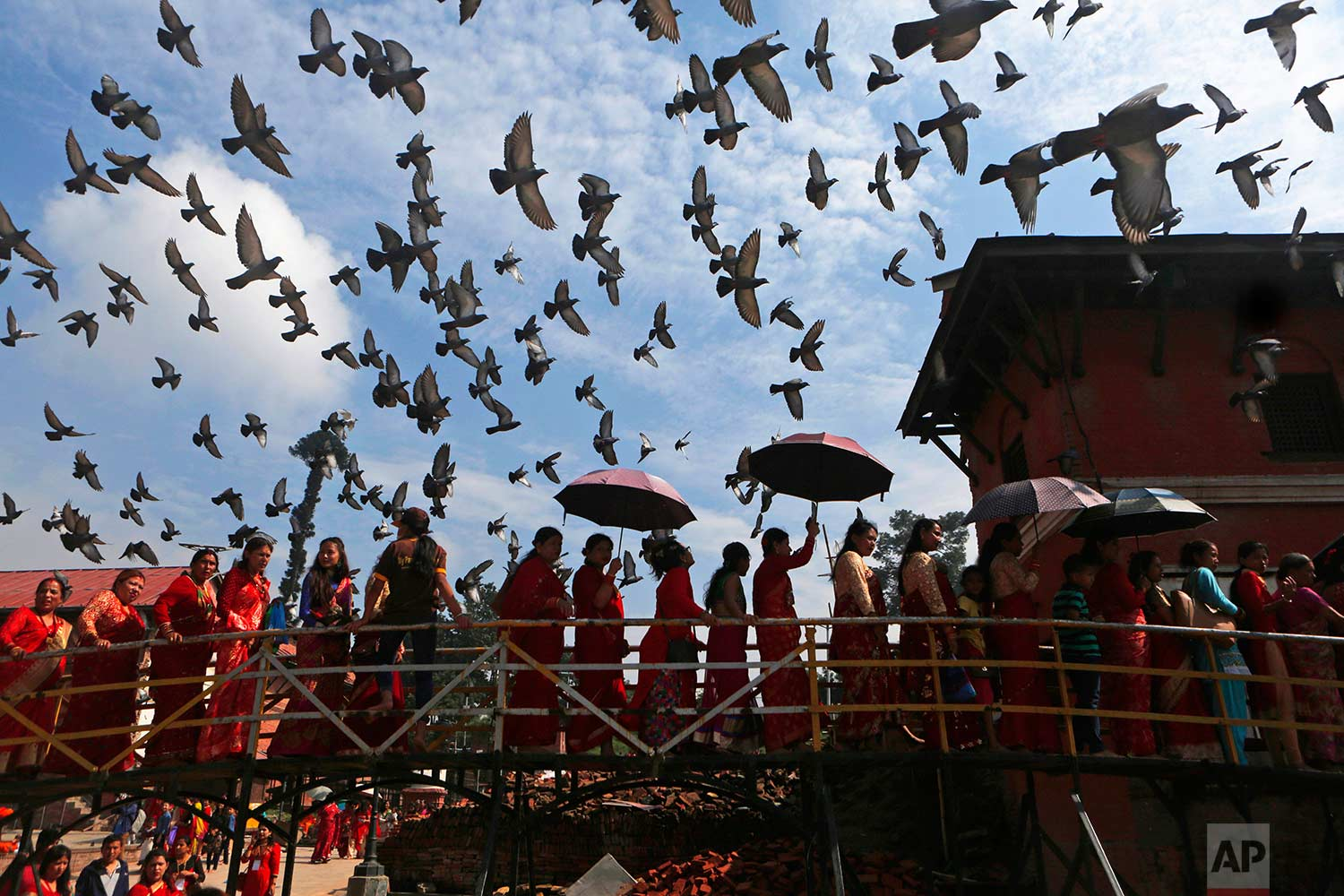 Nepalese Hindu women stand in a line to enter the Pashupatinath temple to offer prayers during celebrations for the festival of Teej in Kathmandu, Nepal, Thursday, Aug. 24, 2017. (AP Photo/Niranjan Shrestha)