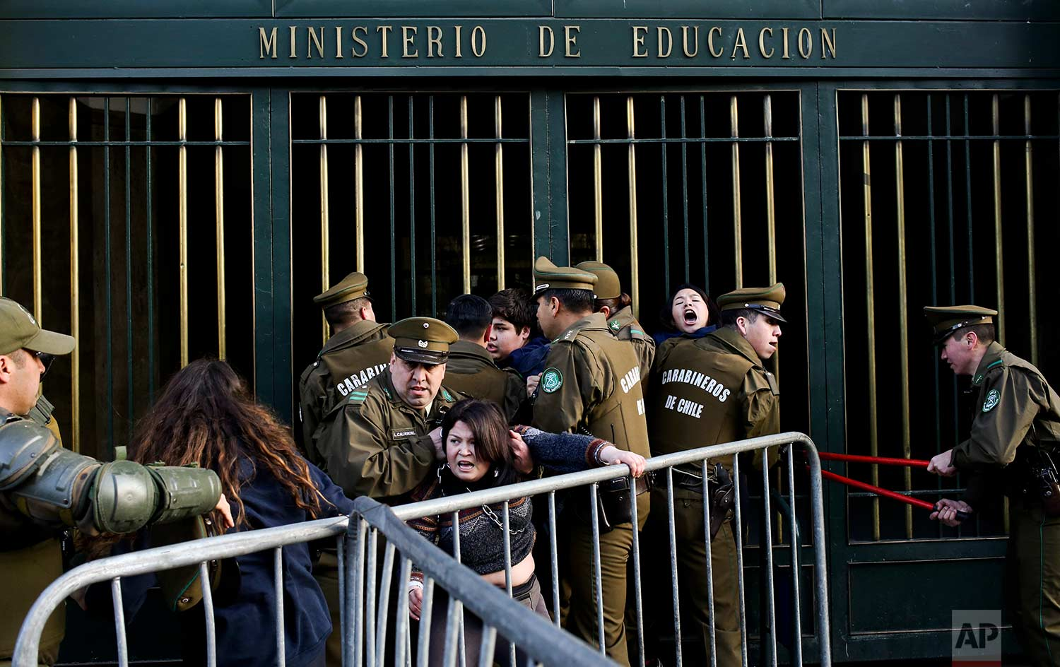 National Police remove protesting high school students who chained themselves to the Ministry of Education building in Santiago, Chile, Wednesday, Aug. 23, 2017. The students are demanding education reform, including free access to school for all ages. (AP Photo/Esteban Felix)