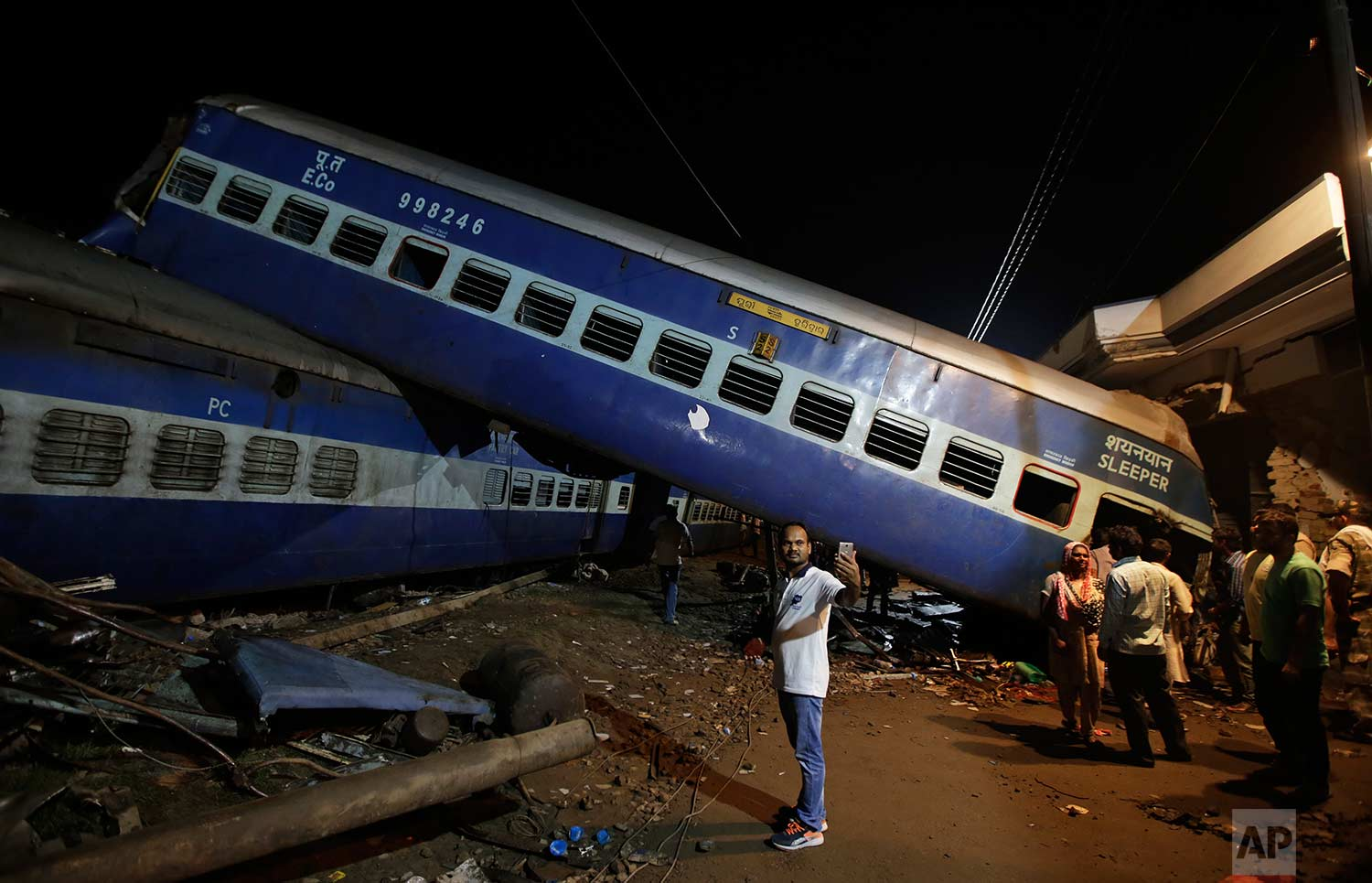 A man takes a selfie photo near the upturned coaches of the Kalinga-Utkal Express after an accident near Khatauli, in the northern Indian state of Uttar Pradesh, India, Sunday, Aug. 20, 2017. (AP Photo/Altaf Qadri)