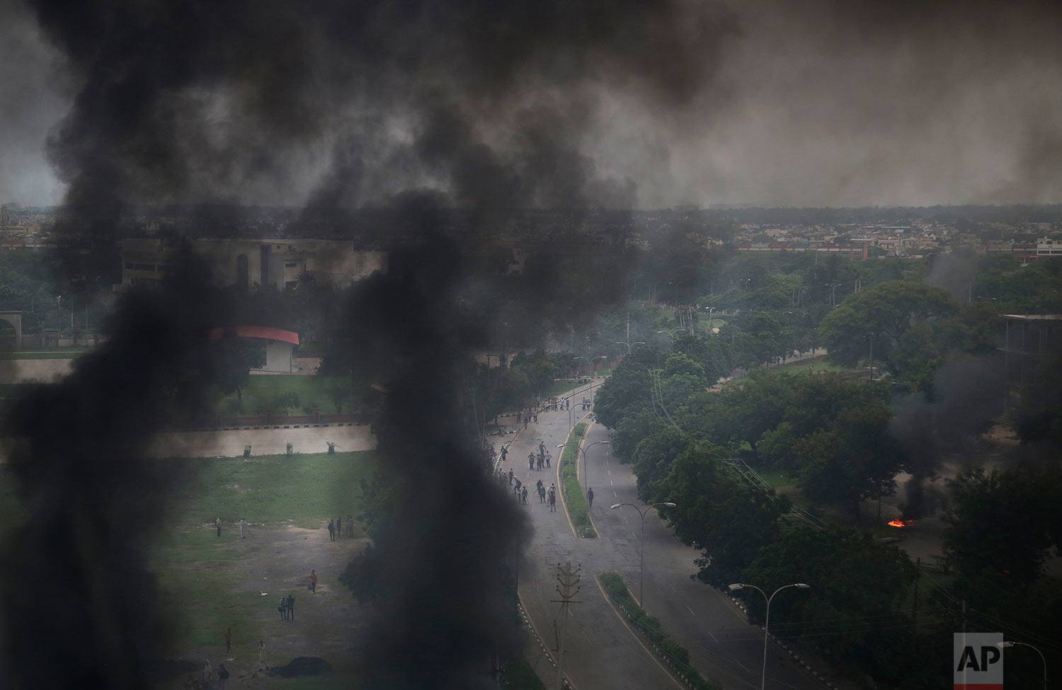 Smoke billows after supporters of the Dera Sacha Sauda sect set vehicles on fire near in Panchkula, India, Friday, Aug. 25, 2017.   (AP Photo/Altaf Qadri)