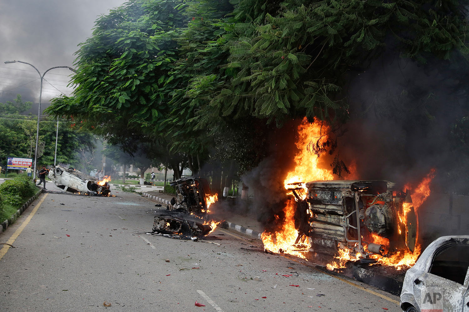 Vehicles set alight by Dera Sacha Sauda sect members burn in the streets of Panchkula, India, Friday, Aug. 25, 2017. (AP Photo/Altaf Qadri)