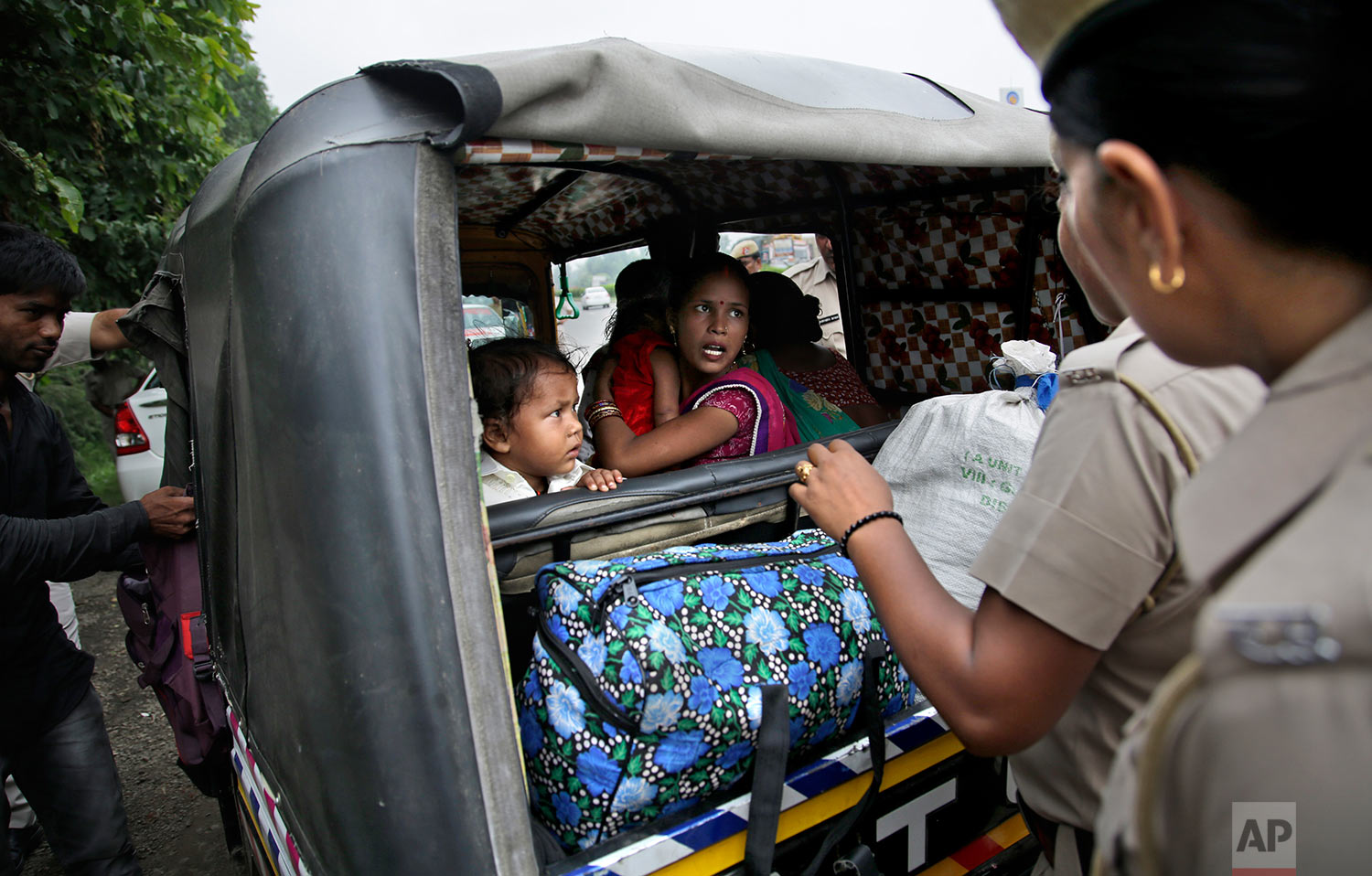 Indian policewomen question a woman passenger in an auto rickshaw as they check for supporters of the Dera Sacha Sauda sect near Panchkula, India, Thursday, Aug. 24, 2017. (AP Photo/Altaf Qadri)