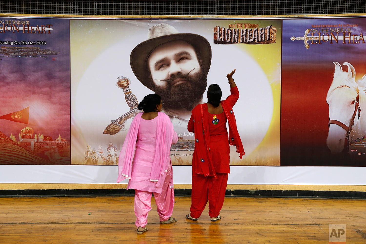 "In this Oct. 5, 2016 photo, devotees of Indian spiritual guru, who calls himself Dr. Saint Gurmeet Singh Ram Rahim Insan, stand near a poster of his film ""MSG: The Warrior Lion Heart,"" in New Delhi, India. (AP Photo/Tsering Topgyal)"