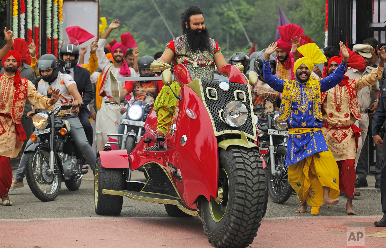 "In this Wednesday, Oct. 5, 2016 photo, Indian spiritual guru, who calls himself Dr. Saint Gurmeet Singh Ram Rahim Insan, rides a motorcycle as he arrives for a press conference ahead of the release of his new film ""MSG: The Warrior Lion Heart,"" in New Delhi, India. (AP Photo/Tsering Topgyal)"