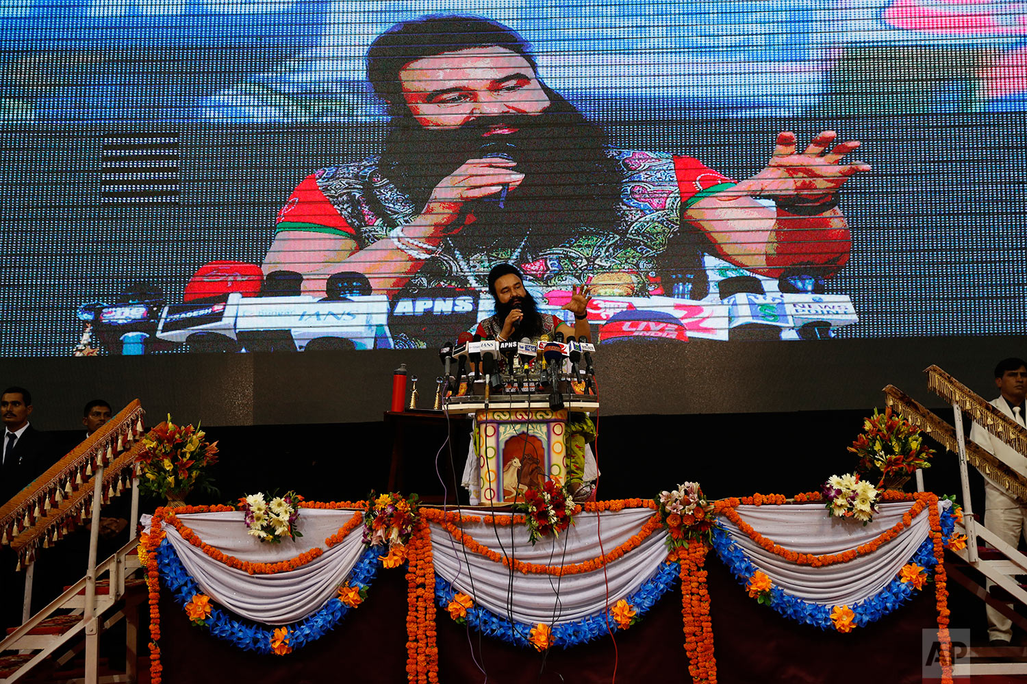In this Oct. 5, 2016 photo, an Indian guru, who calls himself Dr. Saint Gurmeet Singh Ram Rahim Insan, addresses a press conference ahead of releasing his new movie, MSG The Warrior, Lion Heart in New Delhi, India. (AP Photo/Tsering Topgyal)