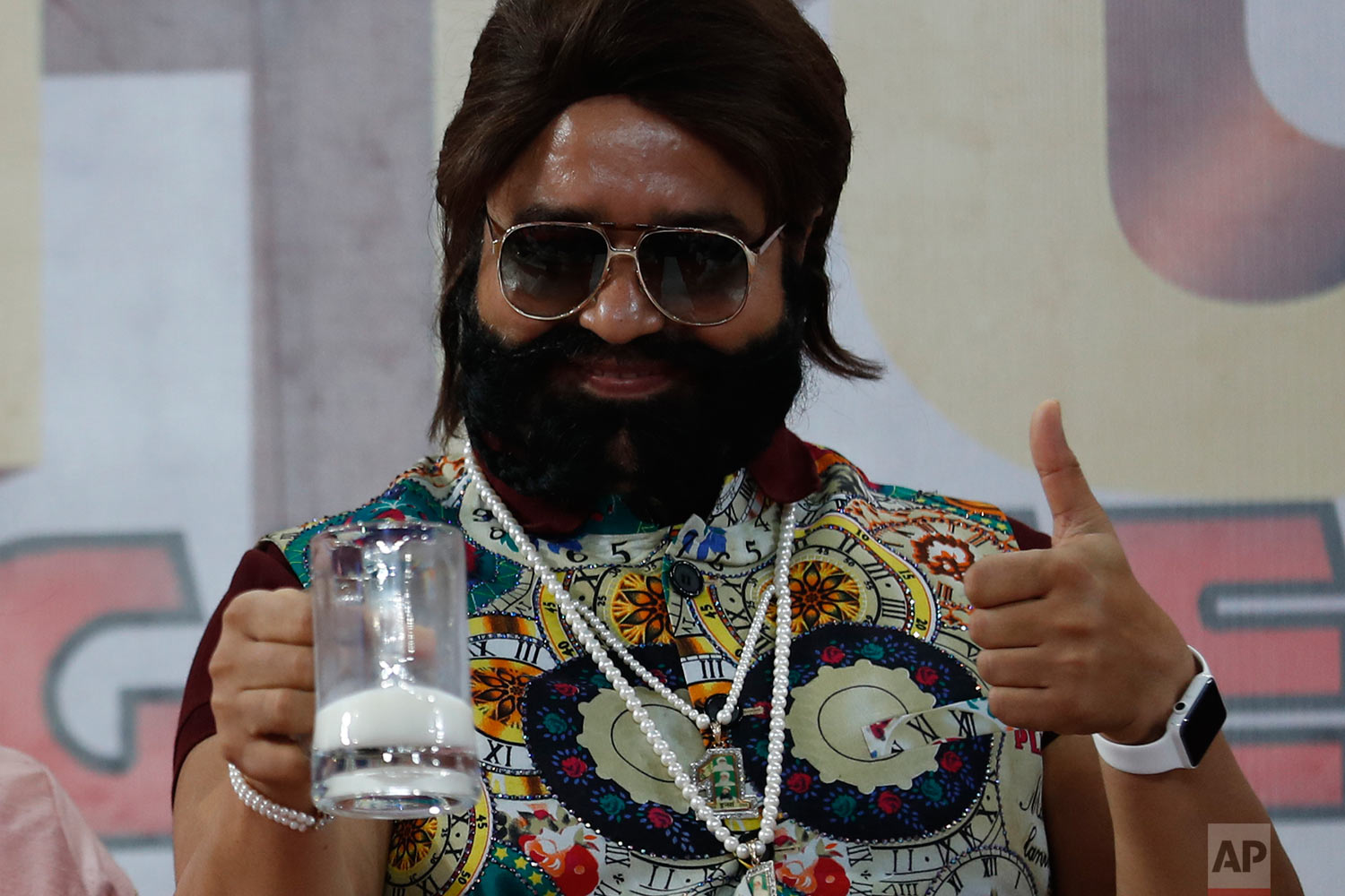 "In this May 17, 2017 photo, Indian spiritual leader turned actor who calls himself Dr. Saint Gurmeet Singh Ram Rahim Insan gestures as he holds up a glass of milk at a ""Cow Milk Party"" during the premiere of the movie ""Jattu Engineer"" in New Delhi, India.  (AP Photo/Tsering Topgyal)"