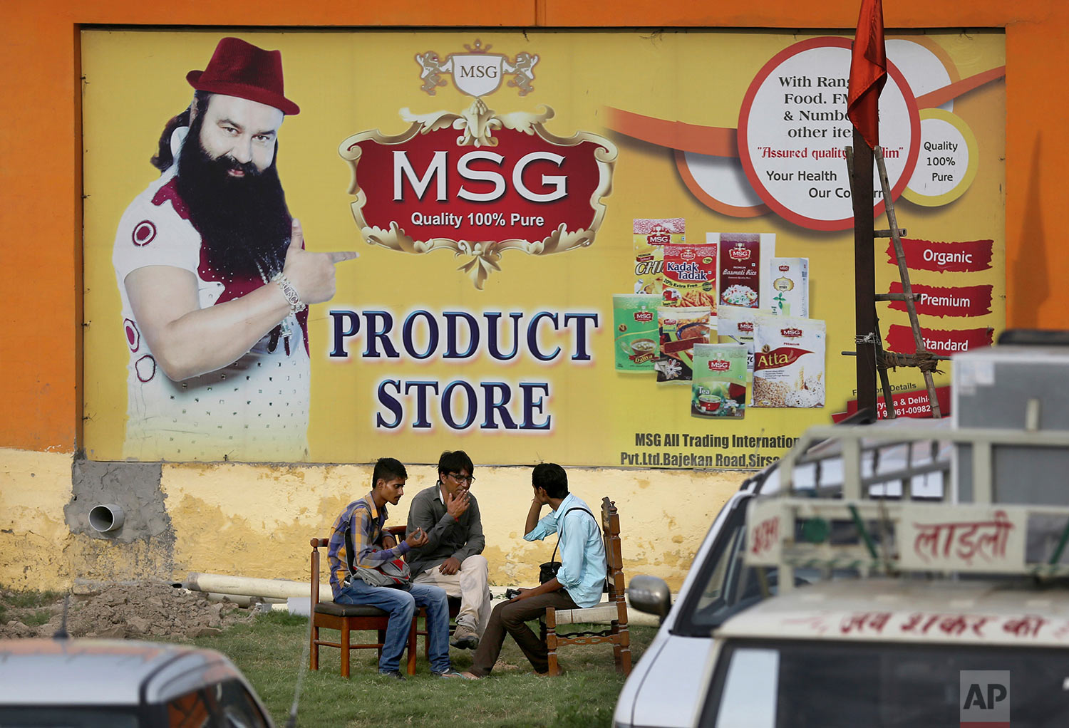 People sit outside the store belonging to Dera Sacha Sauda sect chief Gurmeet Ram Rahim Singh after it was closed down by authorities near Sonipat, India, Saturday, Aug. 26, 2017. (AP Photo/Altaf Qadri)