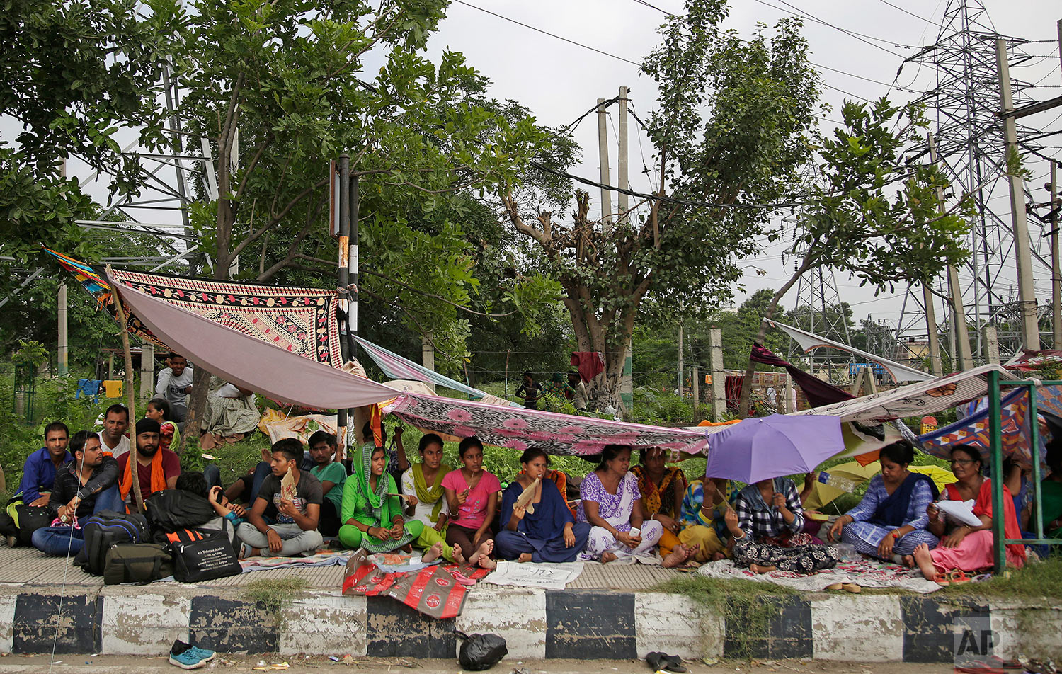 Supporters of the Dera Sacha Sauda sect squat on the roadside leading to an Indian court in Panchkula, India, Thursday, Aug. 24, 2017. (AP Photo/Altaf Qadri)