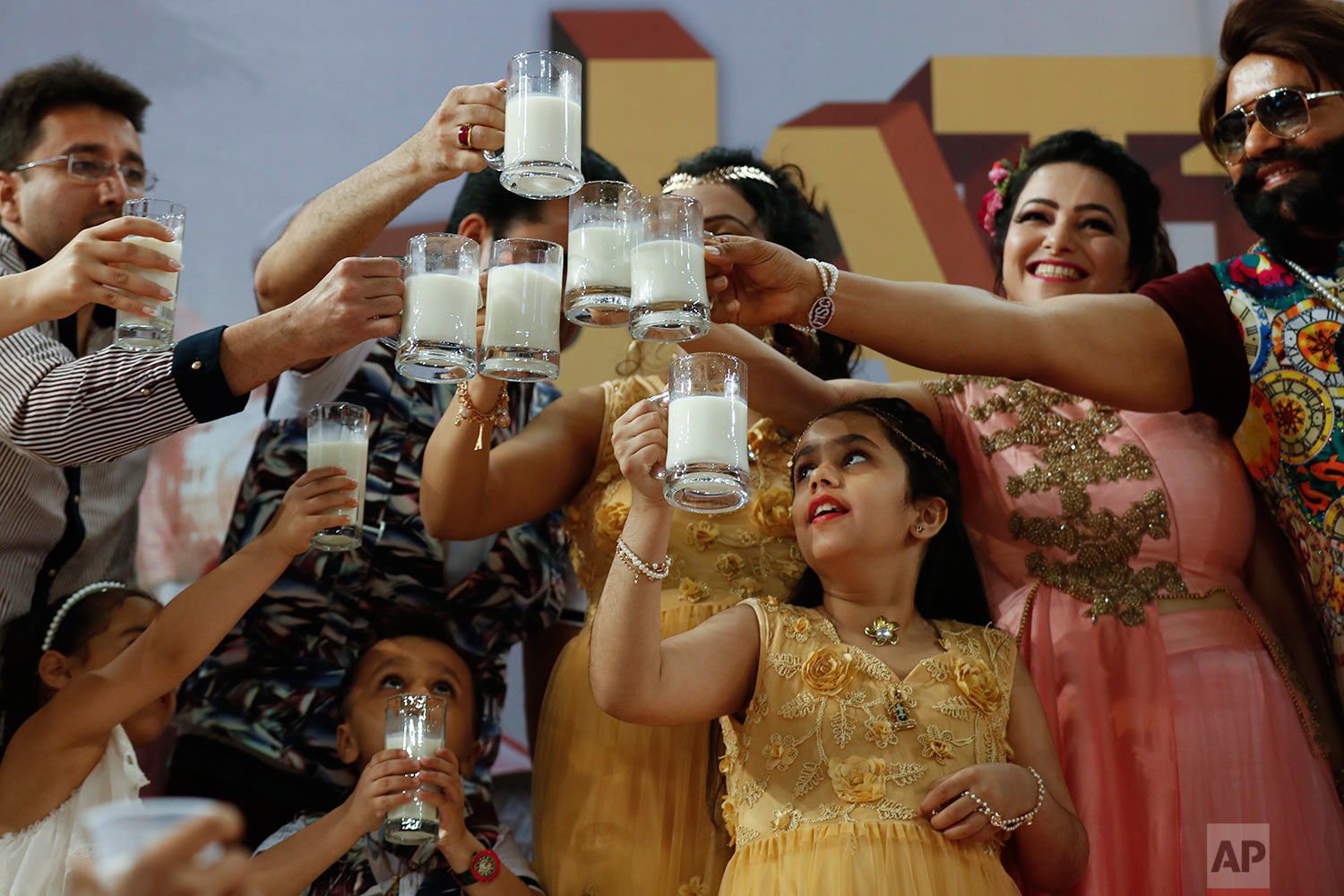 "In this May 17, 2017 photo, Indian spiritual leader who calls himself Dr. Saint Gurmeet Singh Ram Rahim Insan, right, and others raise a toast with glasses of milk as they hold a 'Cow Milk Party' during the premiere of the movie ""Jattu Engineer"" in New Delhi, India.(AP Photo/Tsering Topgyal)"