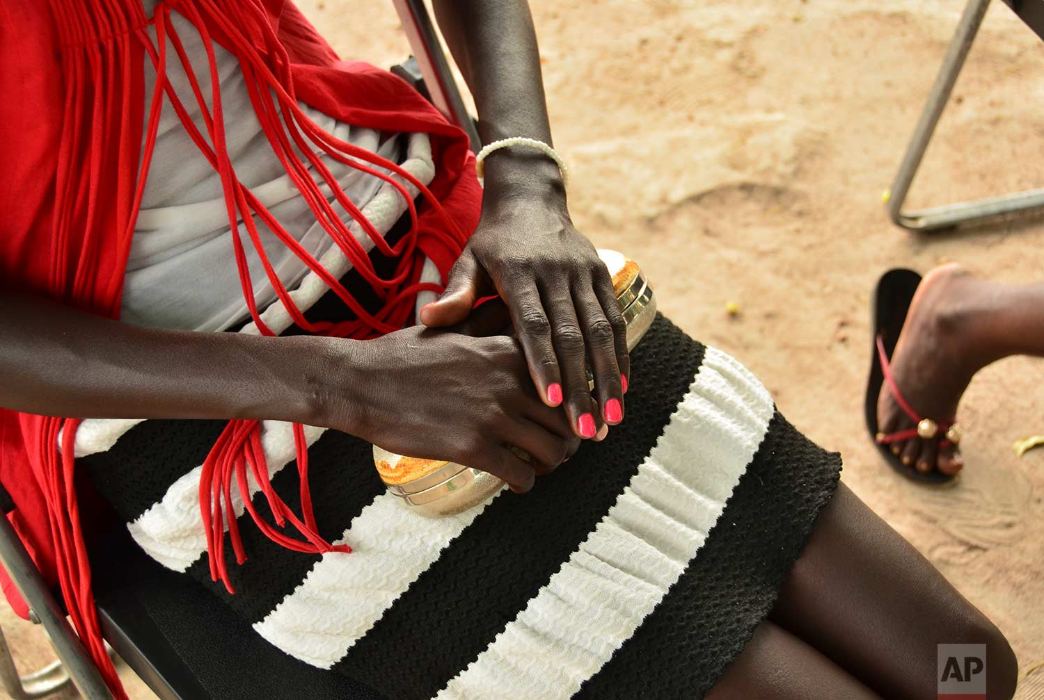 In this photo taken Sunday, July 30, 2017, Eliza, 17, who at age 13 was forced by her father to marry a 35-year-old man from their village in exchange for 50 cattle, recounts her experience to The Associated Press in the town of Rumbek, South Sudan. (AP Photo/Mariah Quesada)