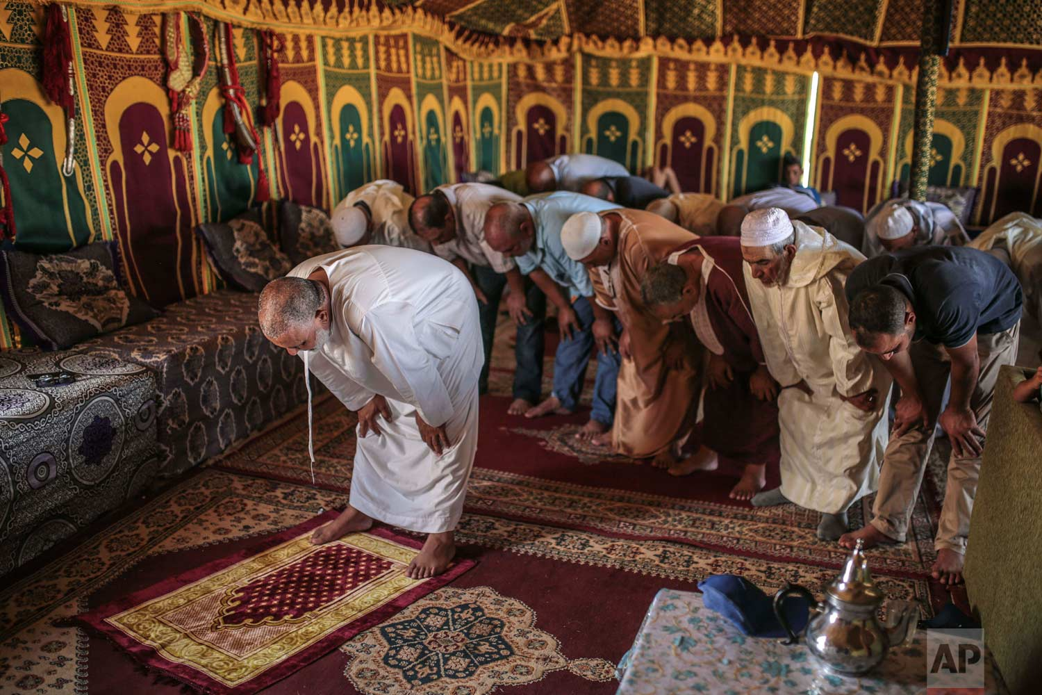 In this Thursday, Aug. 17, 2017 photo, people pray in a tent before the start of Tabourida, a traditional horse riding show also known as Fantasia, in Mansouria, near Casablanca, Morocco. (AP Photo/Mosa'ab Elshamy)