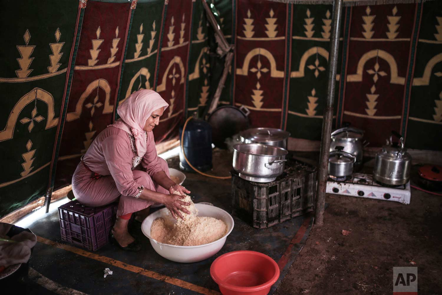 In this Thursday, Aug. 17, 2017 photo, a woman cooks couscous for horsemen taking part in Tabourida, a traditional horse riding show also known as Fantasia, in Mansouria, near Casablanca, Morocco. (AP Photo/Mosa'ab Elshamy)