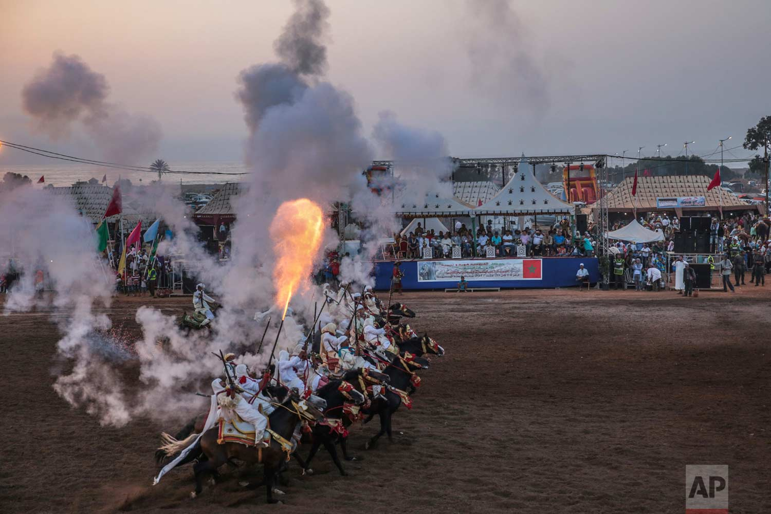 In this Thursday, Aug. 17, 2017 photo, a troupe charges and fires their rifles during Tabourida, a traditional horse riding show also known as Fantasia, in Mansouria, near Casablanca, Morocco. (AP Photo/Mosa'ab Elshamy)