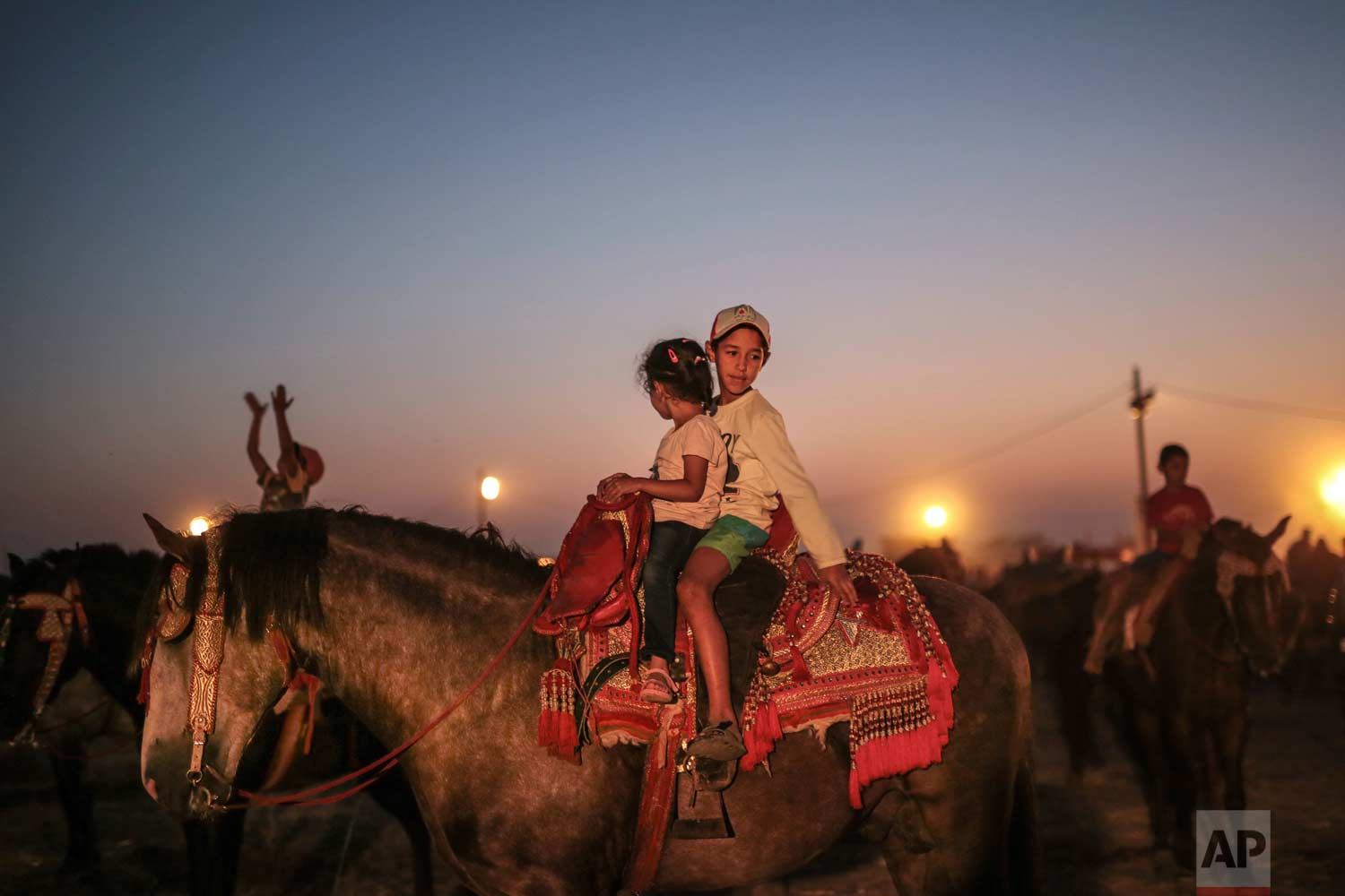 In this Thursday, Aug. 17, 2017 photo, children play on horses, after the end of Tabourida, a traditional horse riding show also known as Fantasia, in Mansouria, near Casablanca, Morocco. (AP Photo/Mosa'ab Elshamy)