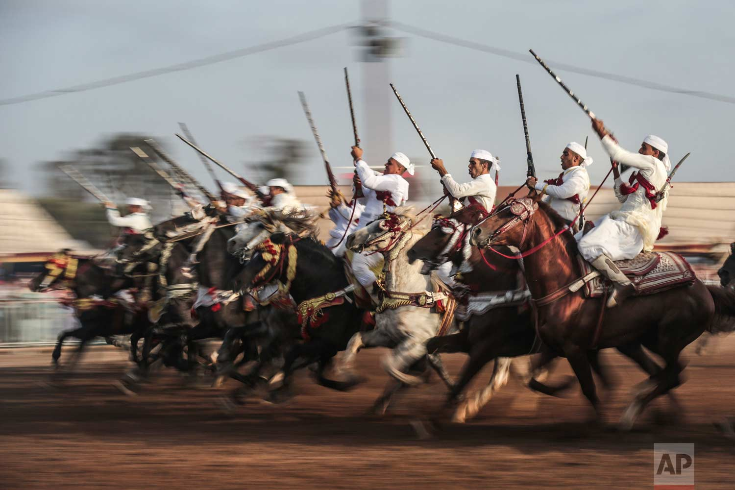 In this Thursday, Aug. 17, 2017 photo, a troupe charges and holds their rifles before firing, during Tabourida, a traditional horse riding show also known as Fantasia, in Mansouria, near Casablanca, Morocco. (AP Photo/Mosa'ab Elshamy)