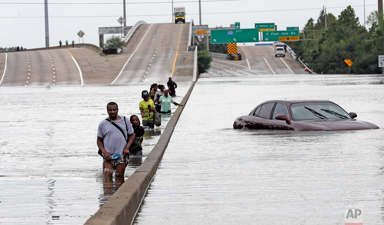 Evacuees wade down a flooded section of Interstate 610 as floodwaters from Tropical Storm Harvey rise Sunday, Aug. 27, 2017, in Houston. (AP Photo/David J. Phillip)