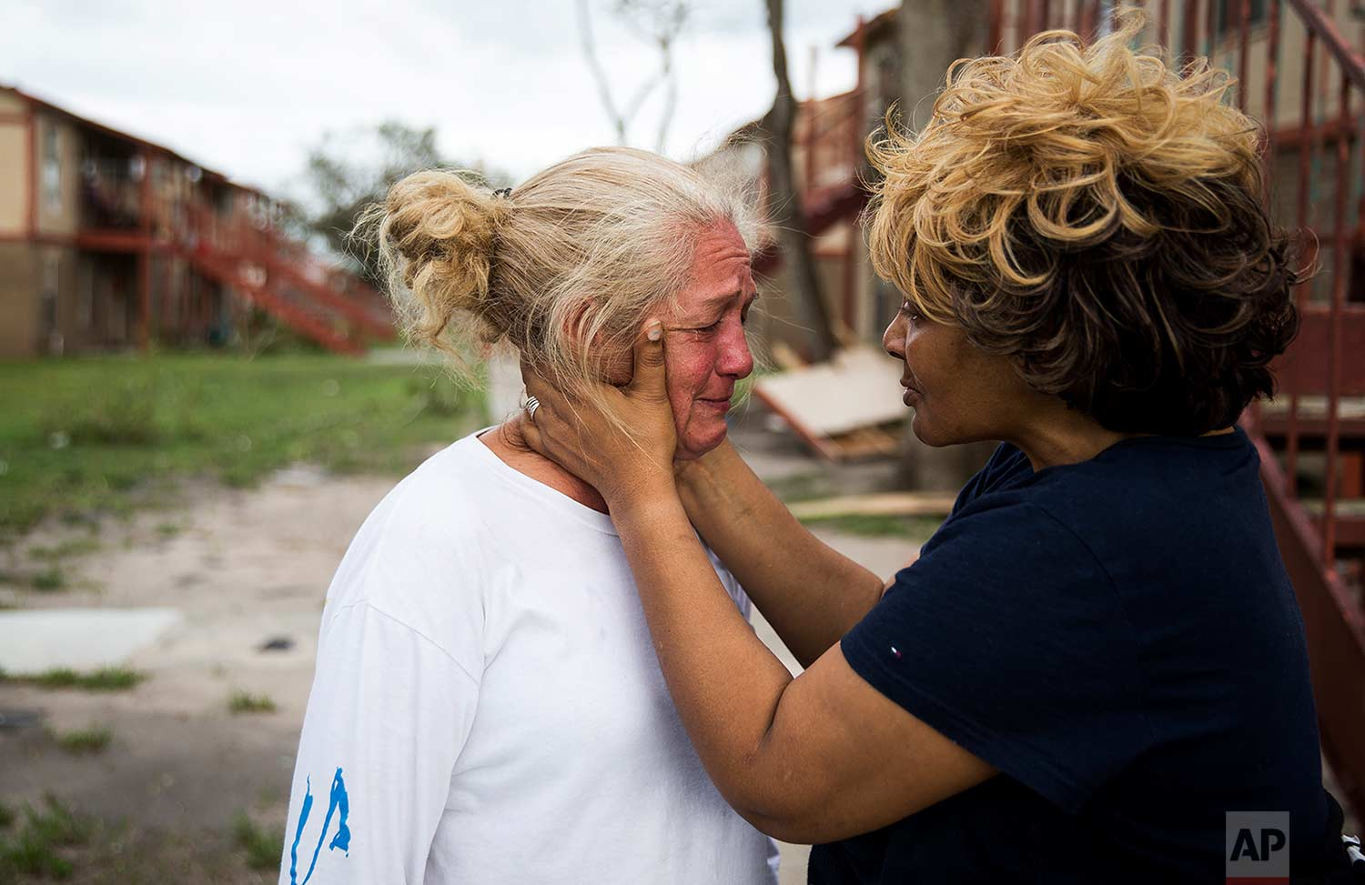 Genice Gipson comforts her lifelong friend, Loretta Capistran, outside of Capistran's apartment complex in Refugio, Texas, on Monday, Aug. 28, 2017. (Nick Wagner/Austin American-Statesman via AP)