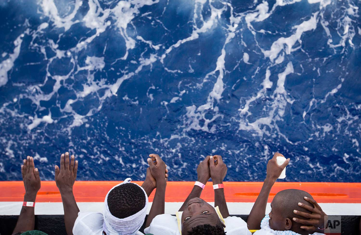 "African migrants stand on the deck of the Aquarius vessel of the ""SOS Mediterranee"" and MSF (Doctors Without Borders) NGOs, in the Mediterranean Sea, southwest of Malta, Thursday, Aug. 31, 2017. (AP Photo/Darko Bandic)"