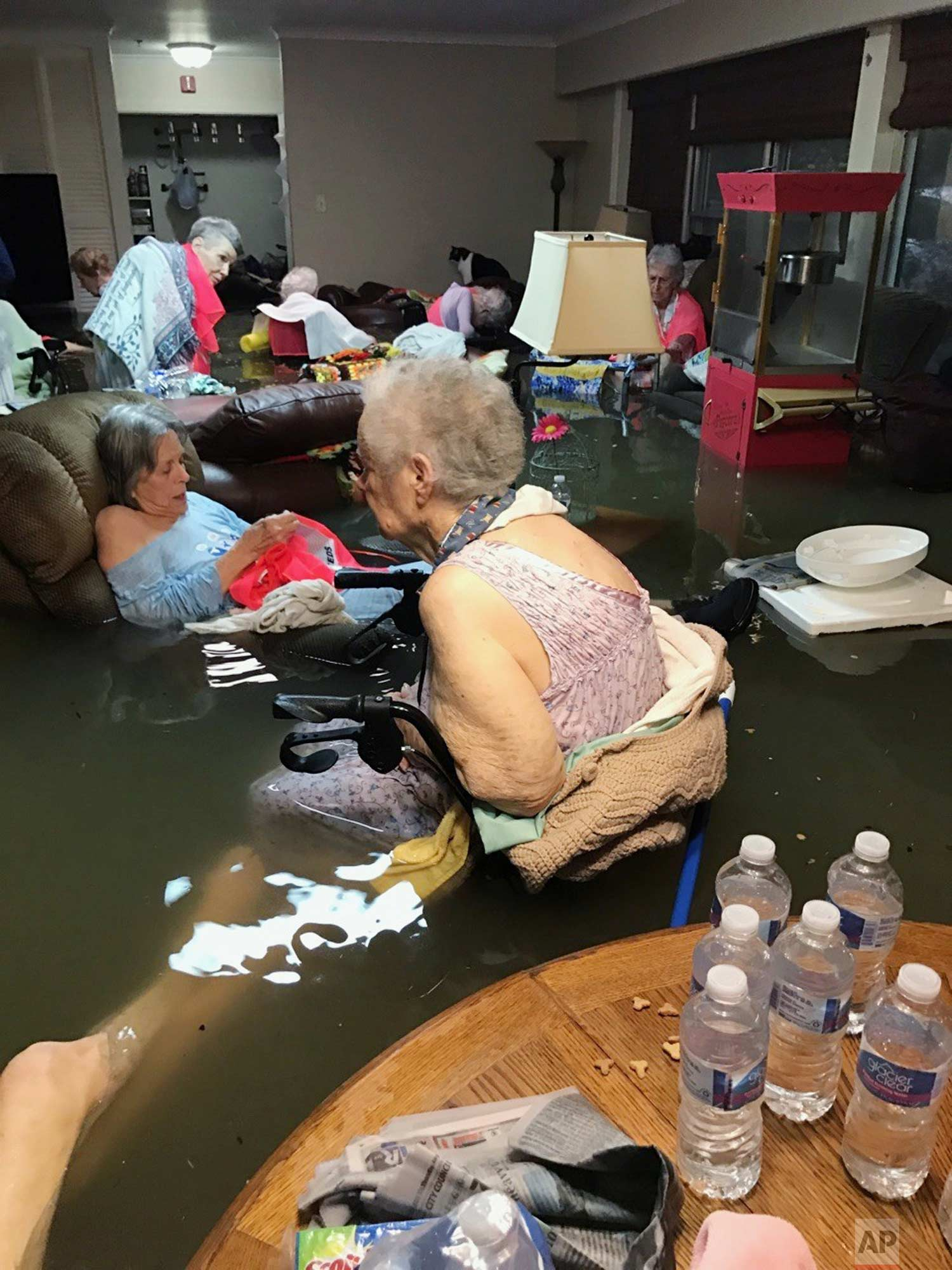 In this photo provided by Trudy Lampson, residents of the La Vita Bella nursing home in Dickinson, Texas, sit in waist-deep flood waters caused by Hurricane Harvey on Sunday, Aug. 27, 2017. Authorities said all the residents were safely evacuated from the facility. (Trudy Lampson via AP)