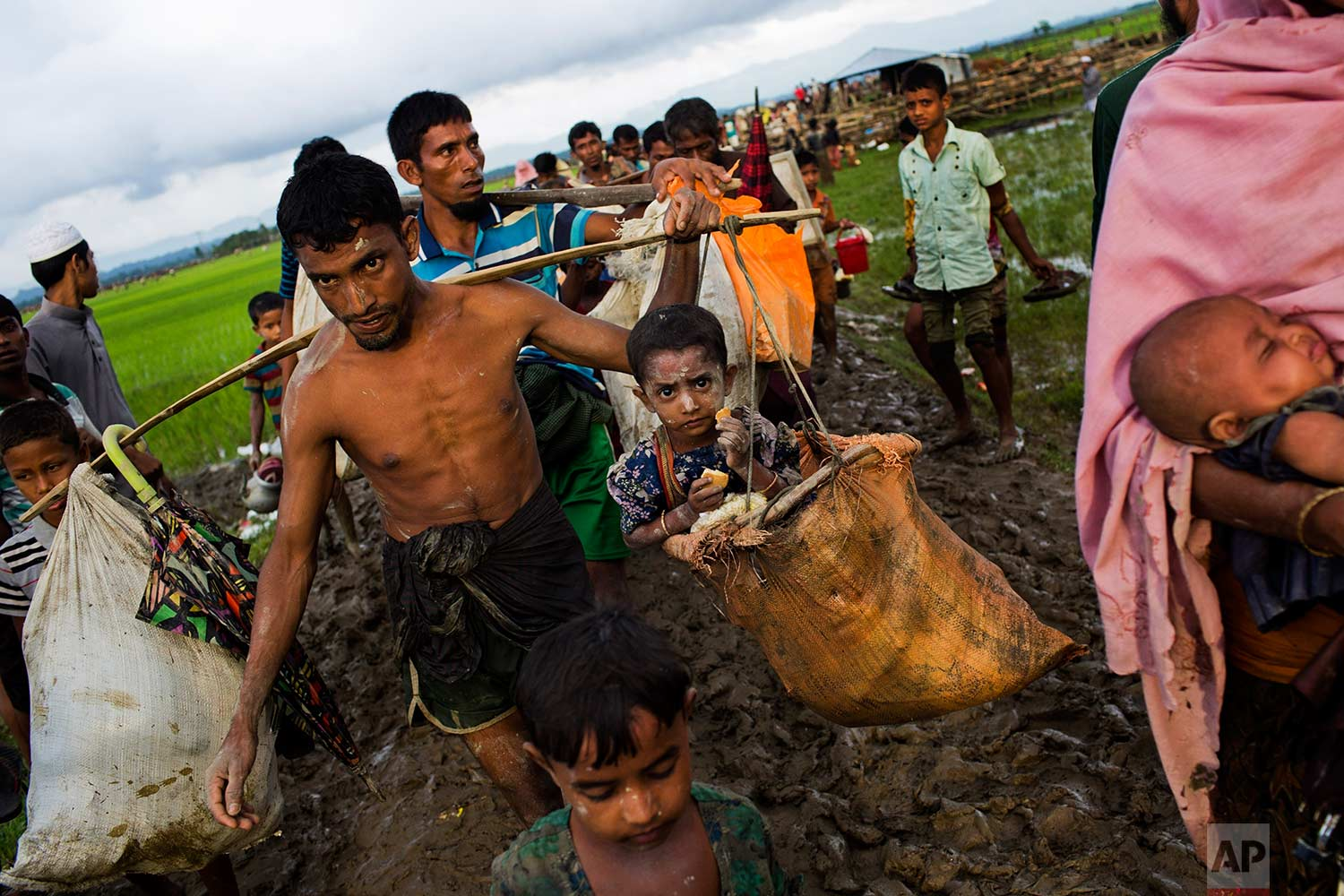 A Rohingya ethnic minority refugee from Myanmar carries a child in a sack and walks through rice fields after crossing over to the Bangladesh side of the border near Cox's Bazar's Teknaf area, Friday, Sept. 1, 2017. Myanmar's military says almost 400 people have died in recent violence in the western state of Rakhine triggered by attacks on security forces by insurgents from the Rohingya. (AP Photo/Bernat Armangue)