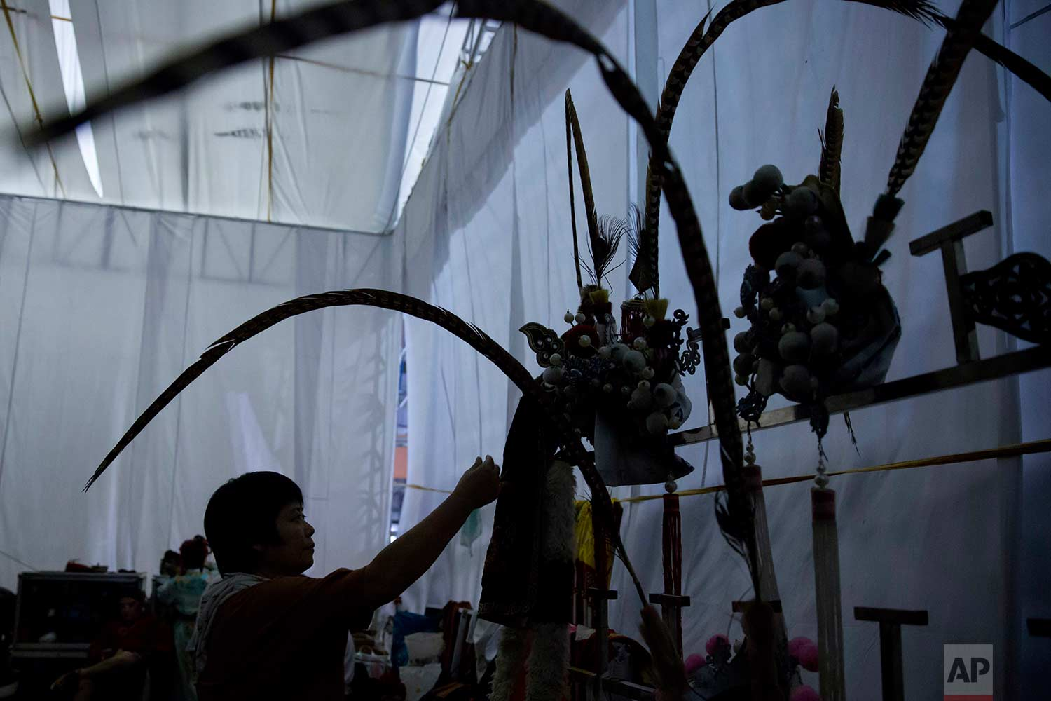 """In this Aug. 30, 2017, photo, Chinese opera costumes are displayed at a makeshift theater during the """"Hungry Ghost Festival"""" in Hong Kong. (AP Photo/Kin Cheung)"""