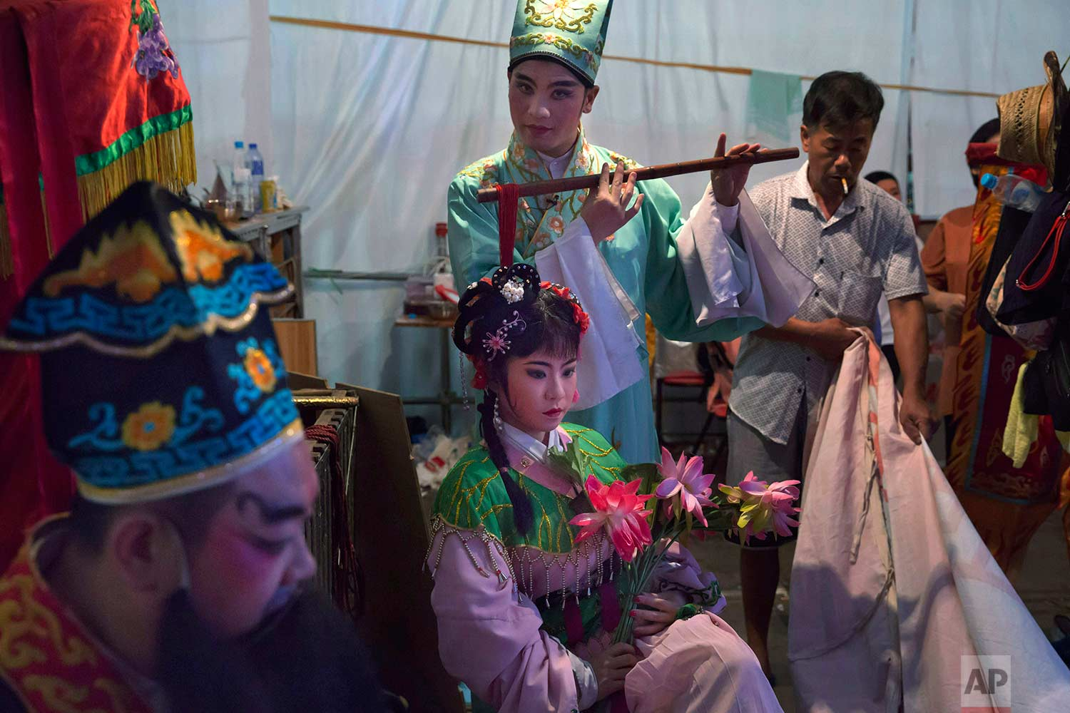 """In this Aug. 30, 2017, photo, Chinese opera performers wait at a makeshift theater during the """"Hungry Ghost Festival"""" in Hong Kong. (AP Photo/Kin Cheung)"""