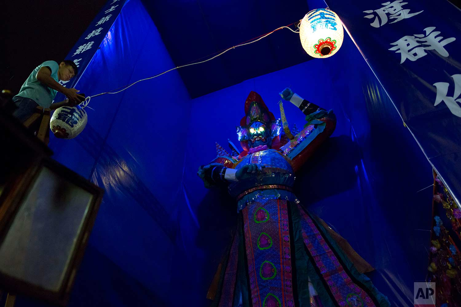 """In this Aug. 31, 2017, photo, a man hangs a lantern in front of a paper reproduction of the """"Ghost King"""" at a makeshift altar during the """"Hungry Ghost Festival"""" in Hong Kong. (AP Photo/Kin Cheung)"""