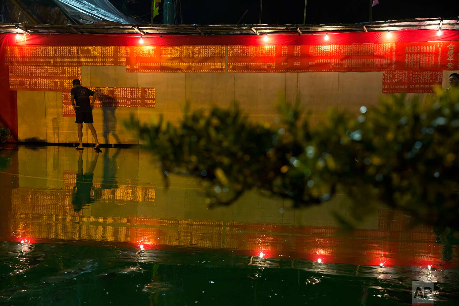 """In this Sept. 3, 2017, photo, a man looks at a list of donors for an opera at a makeshift theater during the """"Hungry Ghost Festival"""" in Hong Kong. (AP Photo/Kin Cheung)"""