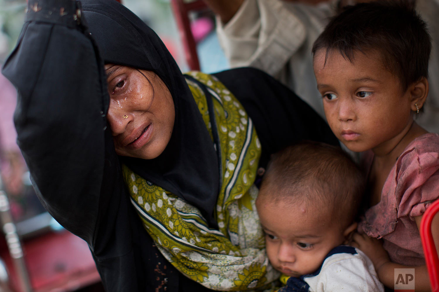 An exhausted Rohingya woman arrives with her children at Kutupalong refugee camp after crossing from Myanmmar to the Bangladesh side of the border, in Ukhia, Tuesday, Sept. 5, 2017. The family said they had lost several family members in Myanmar. Tens of thousands of Rohingya Muslims, fleeing the latest round of violence to engulf their homes in Myanmar, have been walking for days or handing over their meager savings to Burmese and Bangladeshi smugglers to escape what they describe as certain death. (AP Photo/Bernat Armangue)