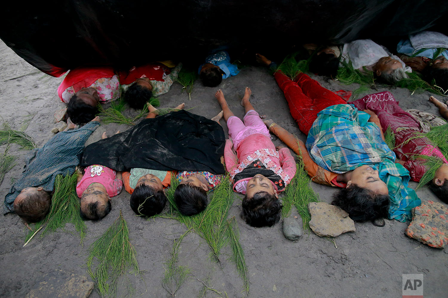 Bodies of Rohingya women and children recovered by Bangladeshi villagers lie on a beach at Shah Porir Deep, in Teknak, Bangladesh, Thursday, Aug.31, 2017. Three boats carrying ethnic Rohingya fleeing violence in Myanmar have capsized in Bangladesh and 26 bodies of women and children have been recovered, officials said Thursday. (AP Photo/Suvra Kanti Das)
