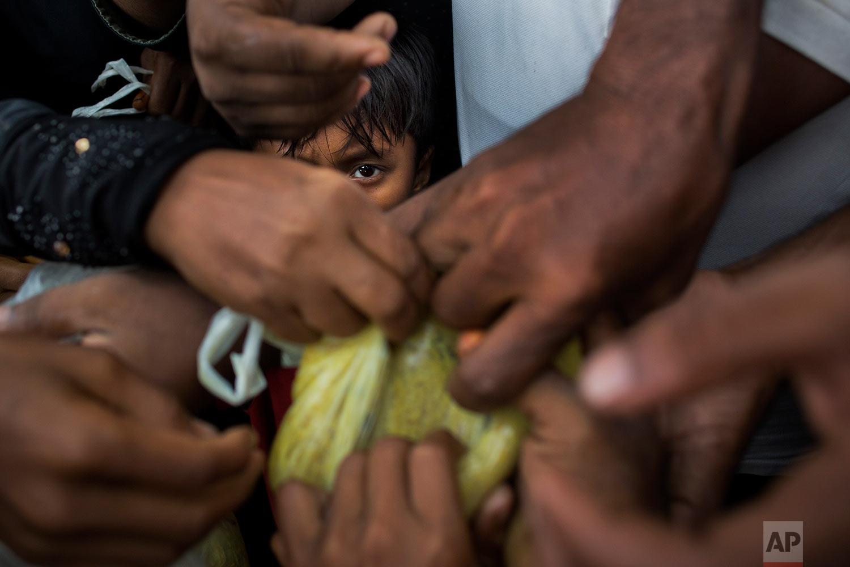 Newly arrived Myanmar's Rohingya ethnic minority refugees scuffle for food rations near Kutupalong refugee camp in Ukhia, Bangladesh, Sunday, Sept. 3, 2017. (AP Photo/Bernat Armangue)