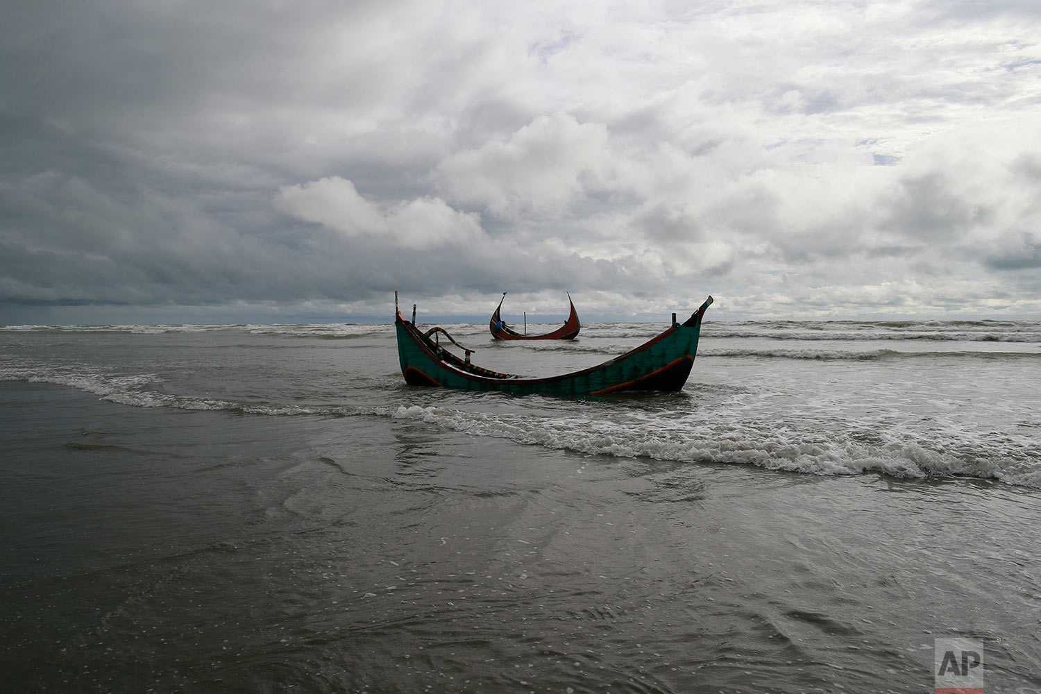 Two among three boats that capsized while being used by fleeing Rohingya is seen on the Bay of Bengal coast, after being recovered by Bangladeshi villagers at Shah Porir Deep, in Teknak, Bangladesh, Thursday, Aug.31, 2017. Three boats carrying ethnic Rohingya fleeing violence in Myanmar have capsized in Bangladesh and 26 bodies of women and children have been recovered, officials said Thursday. Last week, a group of ethnic minority Rohingya insurgents attacked at least two dozen police posts in Myanmar's Rakhine state, triggering fighting with security forces that left more than 100 people dead and forced at least 18,000 Rohingya to flee into neighboring Bangladesh. (AP Photo/Suvra Kanti Das)