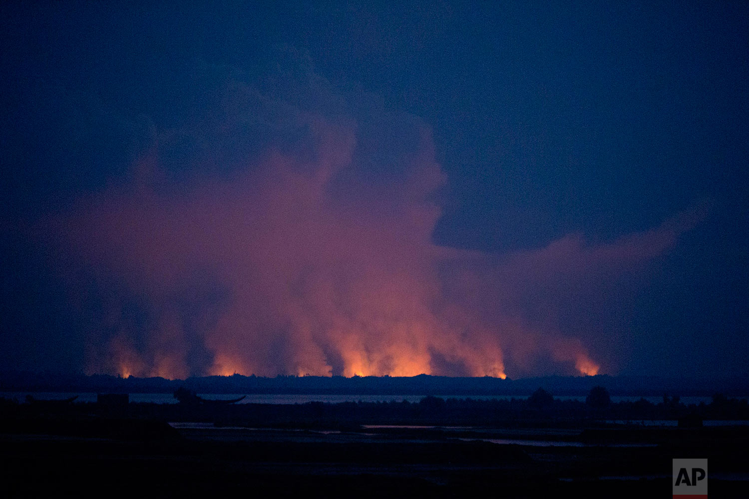 Smoke and flames in Myamar are seen from the Bangladeshi side of the border near Cox's Bazar's Teknaf area, Sunday, Sept. 3, 2017.  (AP Photo/Bernat Armangue)