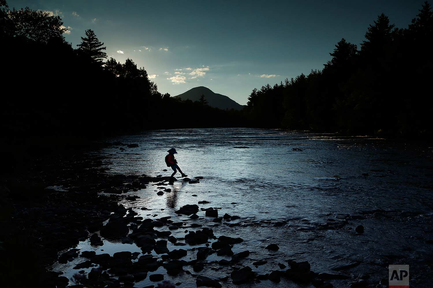 In this Tuesday, Aug. 8, 2017 photo, a youngster explores the Penobscot River's East Branch at the new Katahdin Woods and Waters National Monument near Patten, Maine. Interior Secretary Ryan Zinke wants to retain the newly created national monument, but said he might recommend adjustments to the White House on Thursday, Aug. 24, 2017. (AP Photo/Robert F. Bukaty)
