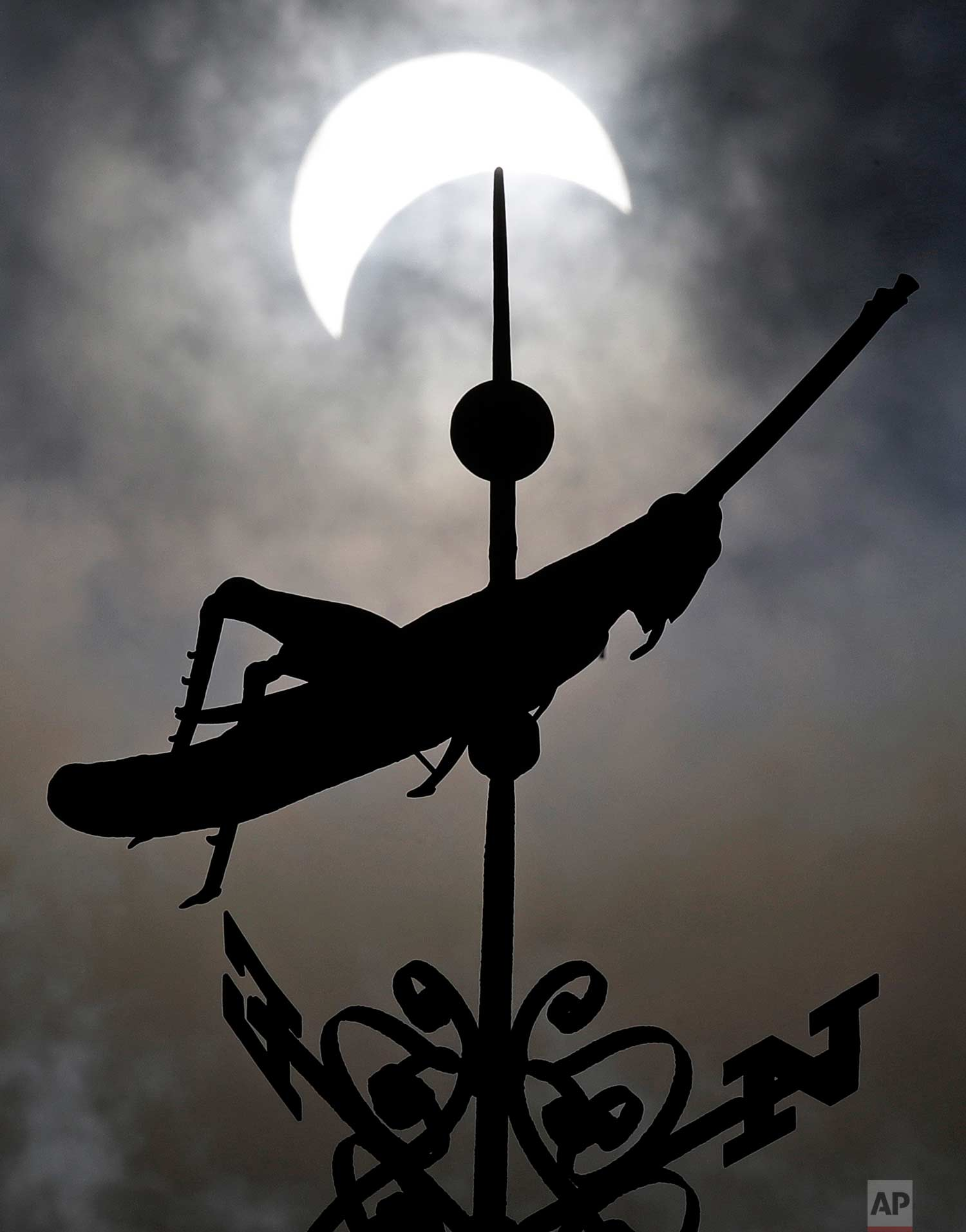 A partial solar eclipse passes over the golden grasshopper weathervane atop historic Faneuil Hall on a cloudy afternoon in Boston, Monday, Aug. 21, 2017. (AP Photo/Charles Krupa)