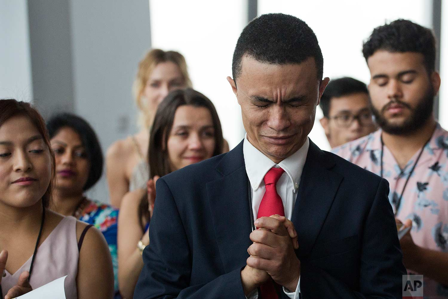 Gleidson Hoffman, originally from Brazil, becomes emotional during his naturalization ceremony, Tuesday, Aug. 15, 2017, in New York. (AP Photo/Mark Lennihan)