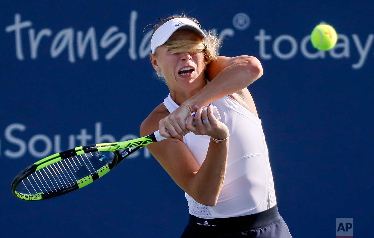 Caroline Wozniacki, of Denmark, returns to Karolina Pliskova, of the Czech Republic, at the Western & Southern Open tennis tournament, Friday, Aug. 18, 2017, in Mason, Ohio. (AP Photo/John Minchillo)