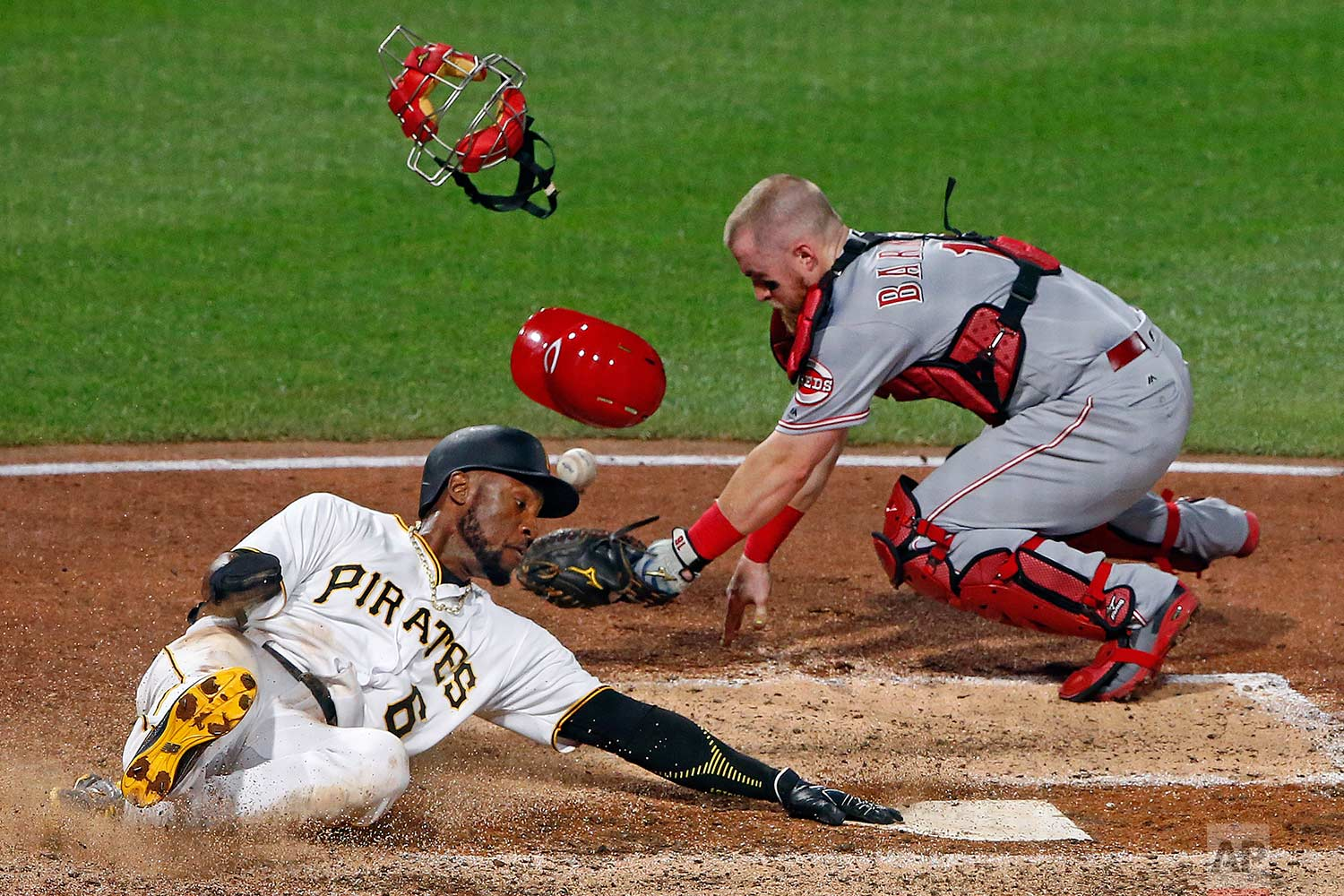 Cincinnati Reds catcher Tucker Barnhart drops the ball after tagging Pittsburgh Pirates' Starling Marte (6), who touches the plate to score the sixth inning of a baseball game in Pittsburgh, Wednesday, Aug. 2, 2017. (AP Photo/Gene J. Puskar)