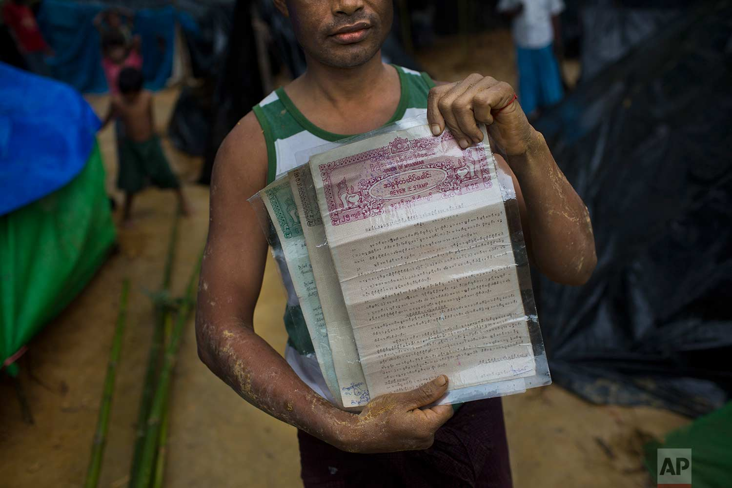 A Rohingya Nur Bashar, who recently crossed over the border from Myanmar into Bangladesh, holds documents of property and land his family owns in Myanmar, in Kutupalong, Bangladesh, Friday, Sept. 8, 2017. (AP Photo/Bernat Armangue)