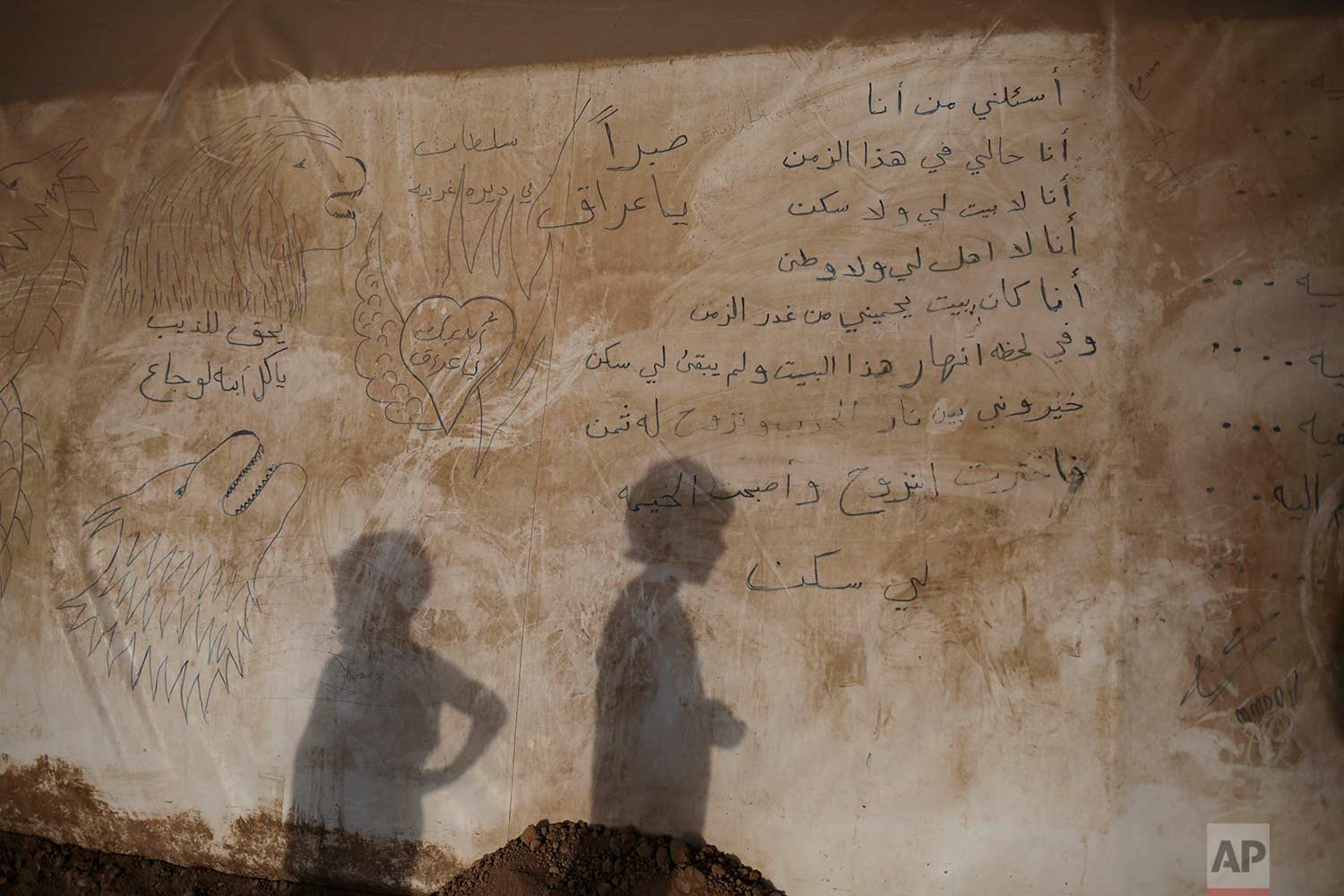 "In this Sunday, July 25, 2017 photo, the shadows of two boys are seen on the side of a tent inside the Khazer camp for displaced people in Northern Iraq. A poem is written in the side of the tent: ""Ask me who I am, I am talking for myself. I am the one who doesn't have a house or a home. I'm the one without relatives and a country. I used to have a house protecting me from the treason of time. In a moment this house collapsed and there's something left for me. I had to choose between the flames of war and the consequences of displacement. I chose displacement and the tent became my home."" (AP Photo/Bram Janssen)"