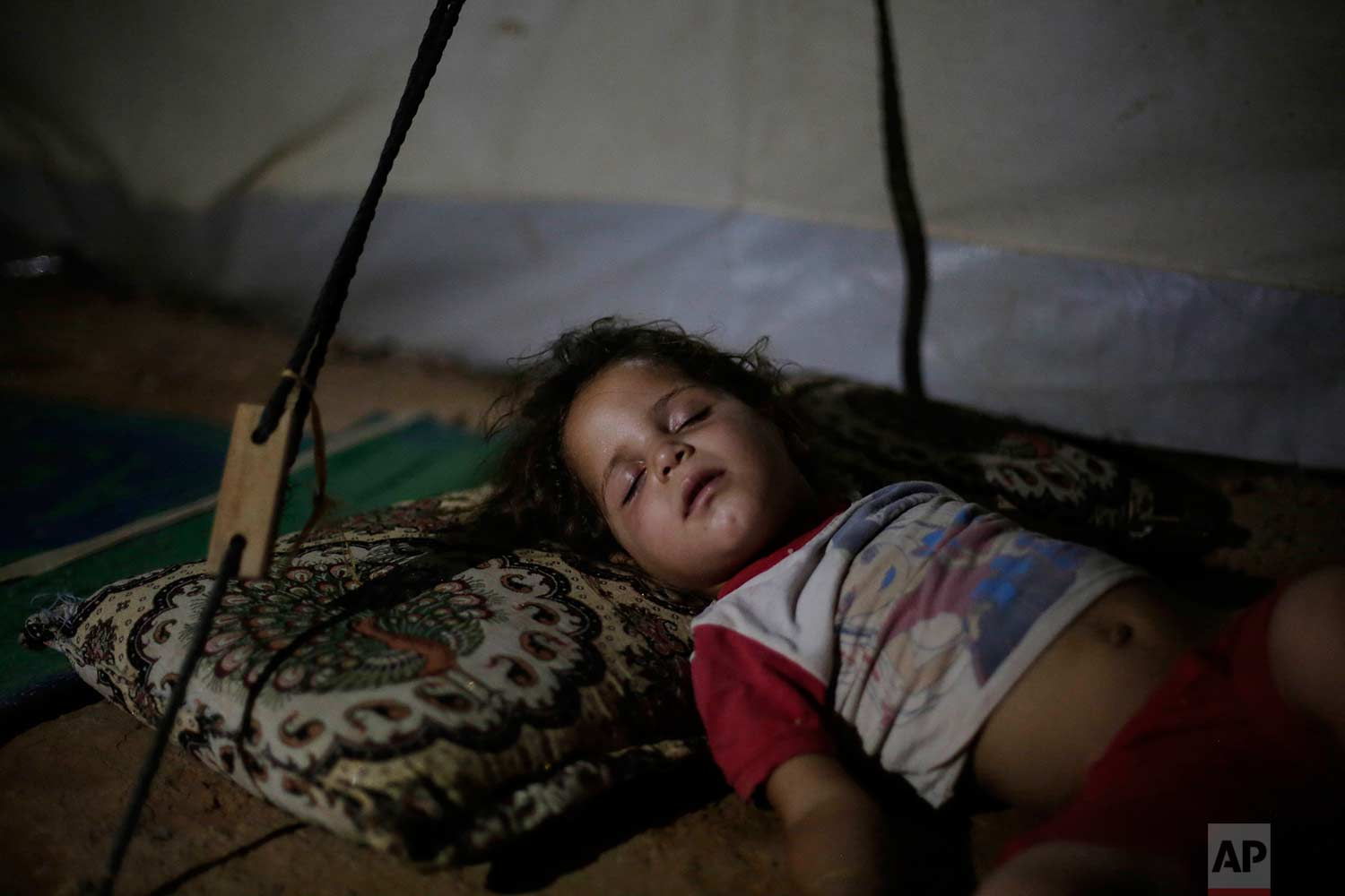 In this Wednesday, Aug. 2, 2017 photo, three year-old Saja Salih sleeps in her tent in the Hassan Sham camp for displaced people in Northern Iraq. Saja, her sister and both parents can't return to their home in Mosul because it was destroyed by an air strike. (AP Photo/Bram Janssen)