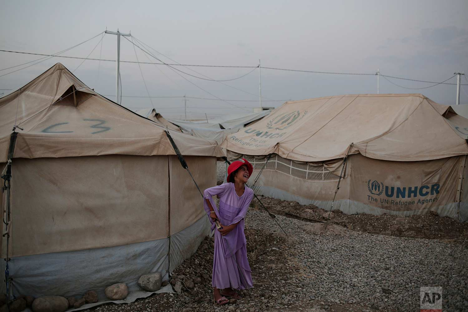 In this Wednesday, Aug. 2, 2017 photo, seven year-old Ragad Ibrahim from Mosul laughs while standing next to her tent in the Hassan Sham camp in northern Iraq. (AP Photo/Bram Janssen)