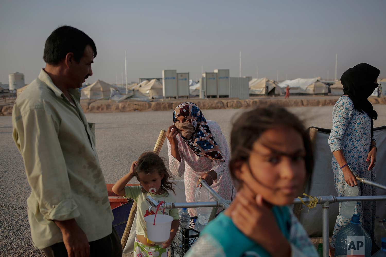 In this Saturday, July 22, 2017 photo, a family gets water inside the Hassan Sham camp in northern Iraq. (AP Photo/Bram Janssen)