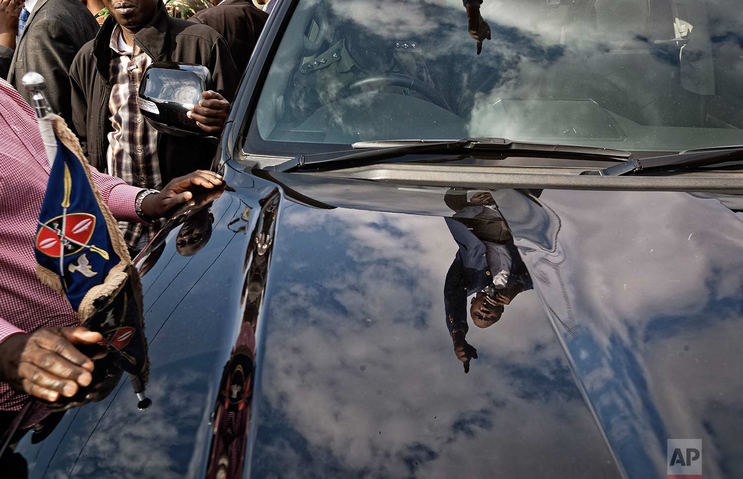 "Kenya's President Uhuru Kenyatta, seen reflected in the hood of a presidential vehicle on which he is standing, addresses supporters on a street in Ongata Rongai, on the outskirts of Nairobi, Kenya Tuesday, Sept. 5, 2017. Kenya faces an Oct. 17 vote after the Supreme Court nullified Kenyatta's re-election, but opposition leader Raila Odinga said Tuesday he does not accept the date, demanding reforms to the electoral commission and other ""legal and constitutional guarantees."" (AP Photo/Ben Curtis)"