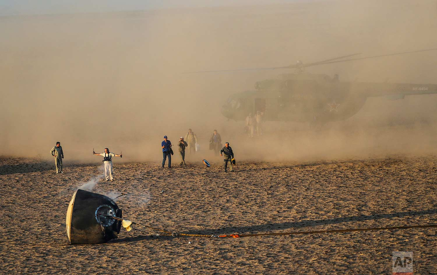 A search and rescue team works on the site of landing of Russian Soyuz MS-04 space capsule in a remote area outside the town of Dzhezkazgan, Kazakhstan, Sunday, Sept. 3, 2017. The Soyuz capsule carrying Astronauts Peggy Whitson and Jack Fischer of NASA and Fyodor Yurchikhin of the Russian space agency Roscosmos safely returned to Earth in the Kazakh steppe. (Sergei Ilnitsky/Pool via AP)