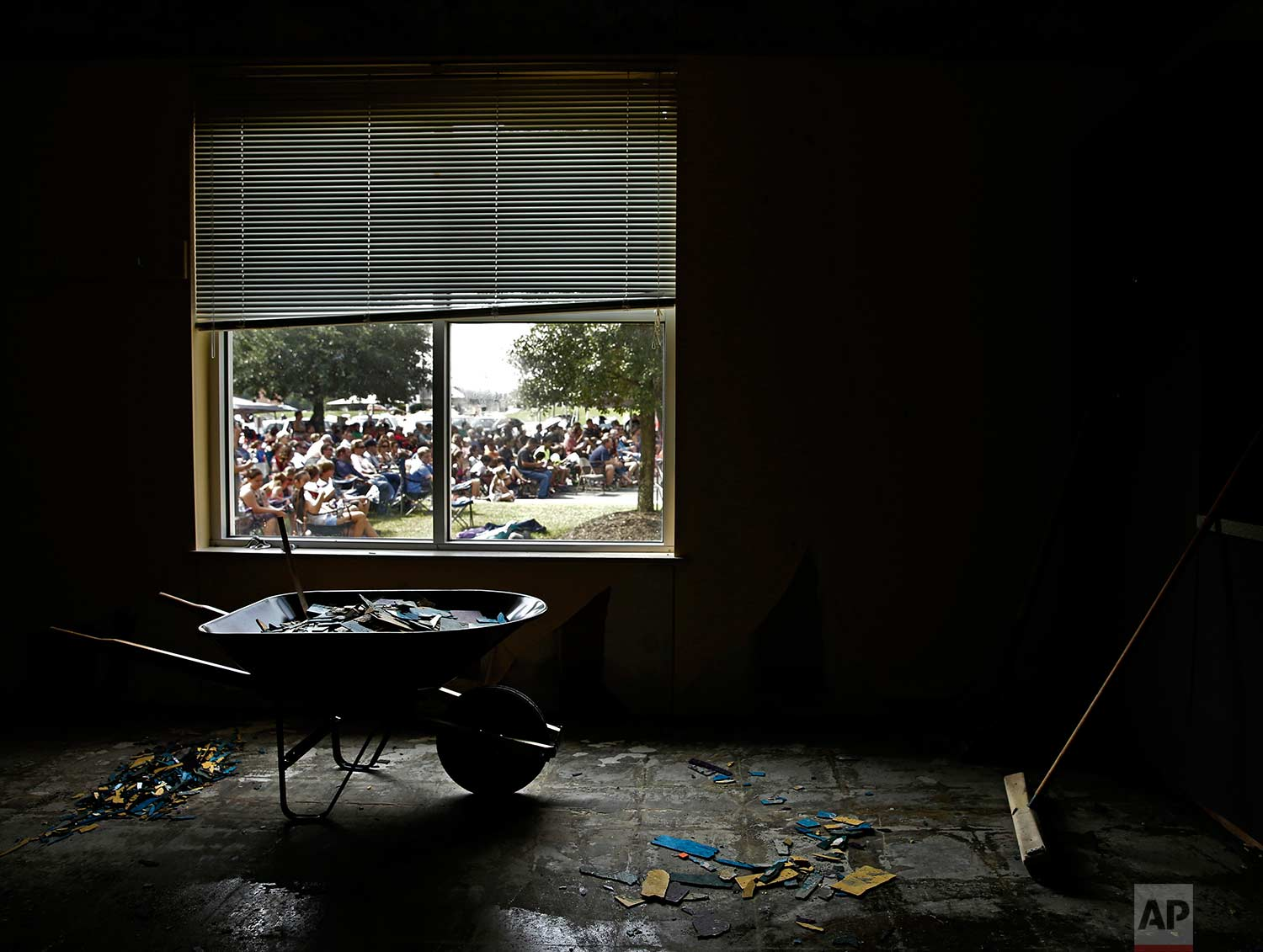 Church members are seen through the window of a water damaged room as they gather in the parking lot of the First Baptist Church for a service Sunday, Sept. 3, 2017, in Humble, Texas. The church building was flooded with two feet of water during Hurricane Harvey, prompting services to be held outside. (AP Photo/Charlie Riedel)