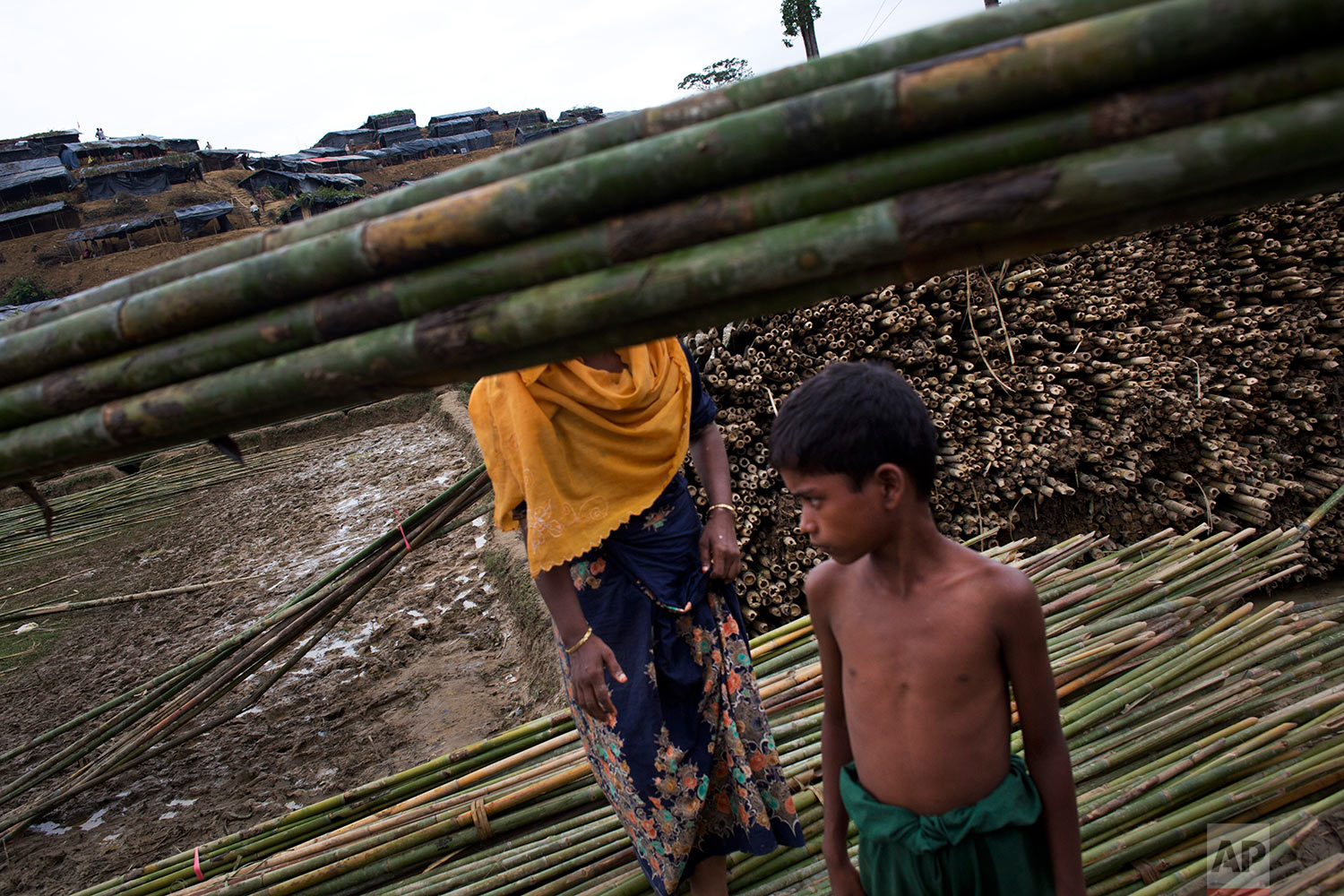 A Rohingya boy stands near bamboo poles used for building tents at a new refugee camp in Ukhia, Bangladesh, Saturday, Sept. 9, 2017. (AP Photo/Bernat Armangue)